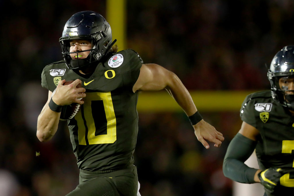 Justin Herbert #10 of the Oregon Ducks runs with the ball to score a 30 yard touchdown against the Wisconsin Badgers during the fourth quarter in the Rose Bowl game presented by Northwestern Mutual at Rose Bowl on Jan. 1, 2020 in Pasadena, Calif.