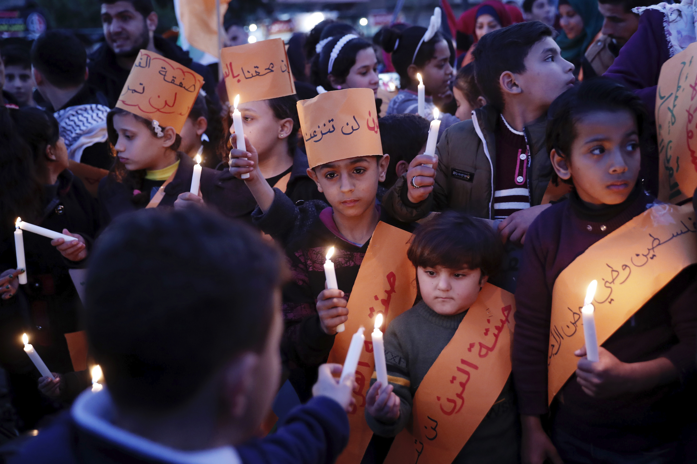 Protesters hold candles during a protest against the Mideast plan announced by the U.S. President Donald Trump, at the road in Jebaliya refugee camp, Gaza Strip, Jan. 30, 2020. Trump's Mideast plan would create a disjointed Palestinian state with a capital on the outskirts of east Jerusalem, beyond the separation barrier built by Israel.