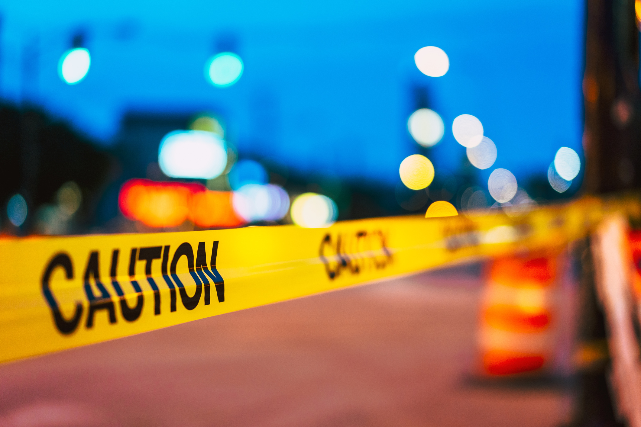 Defocused image of police tape behind city lights