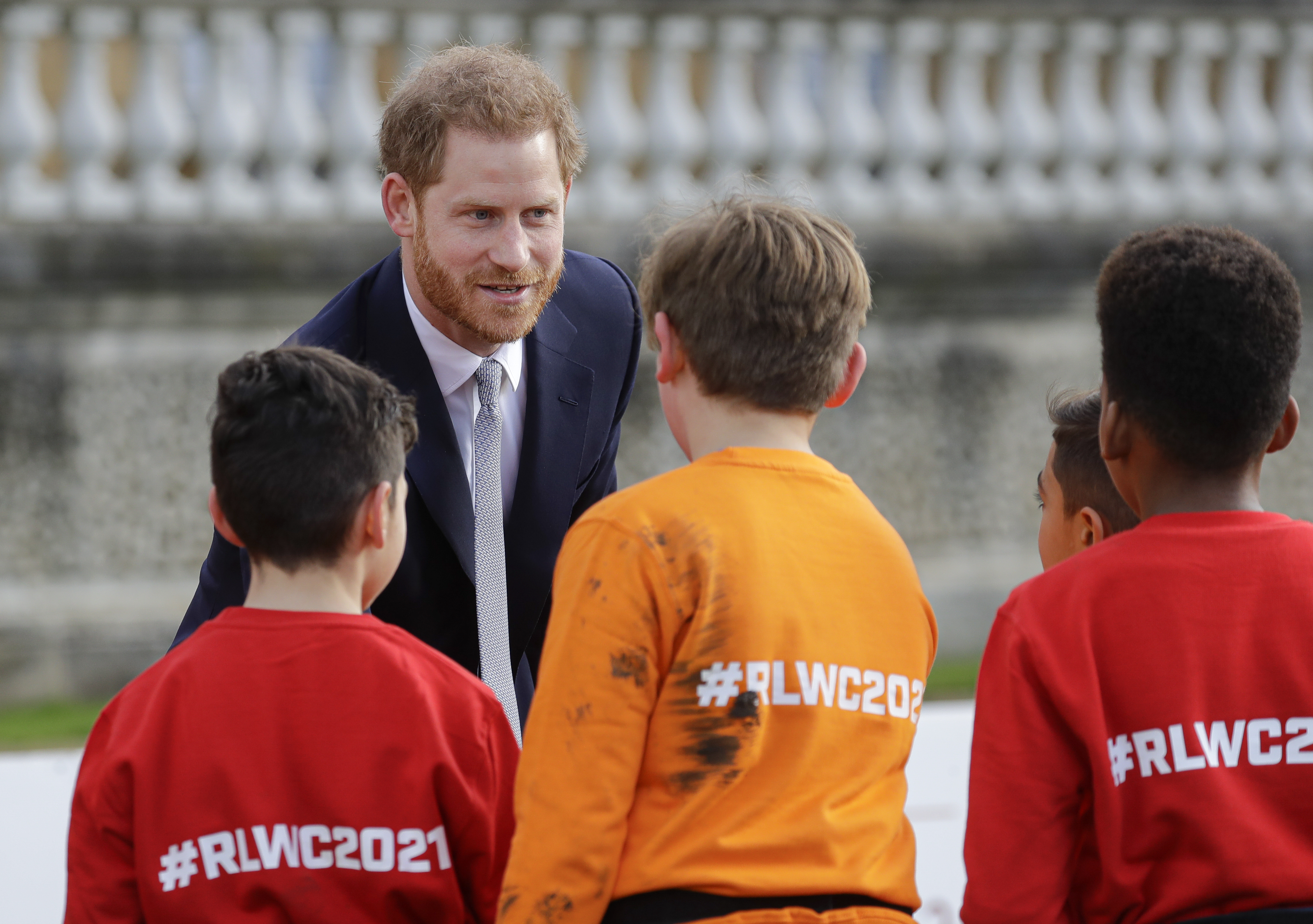 Britain's Prince Harry greets schoolchildren in the gardens at Buckingham Palace in London, Thursday, Jan. 16, 2020.