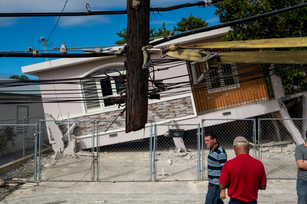 People pass by a house damaged by a 5.8 earthquake in Guanica, Puerto Rico on January 6, 2020.