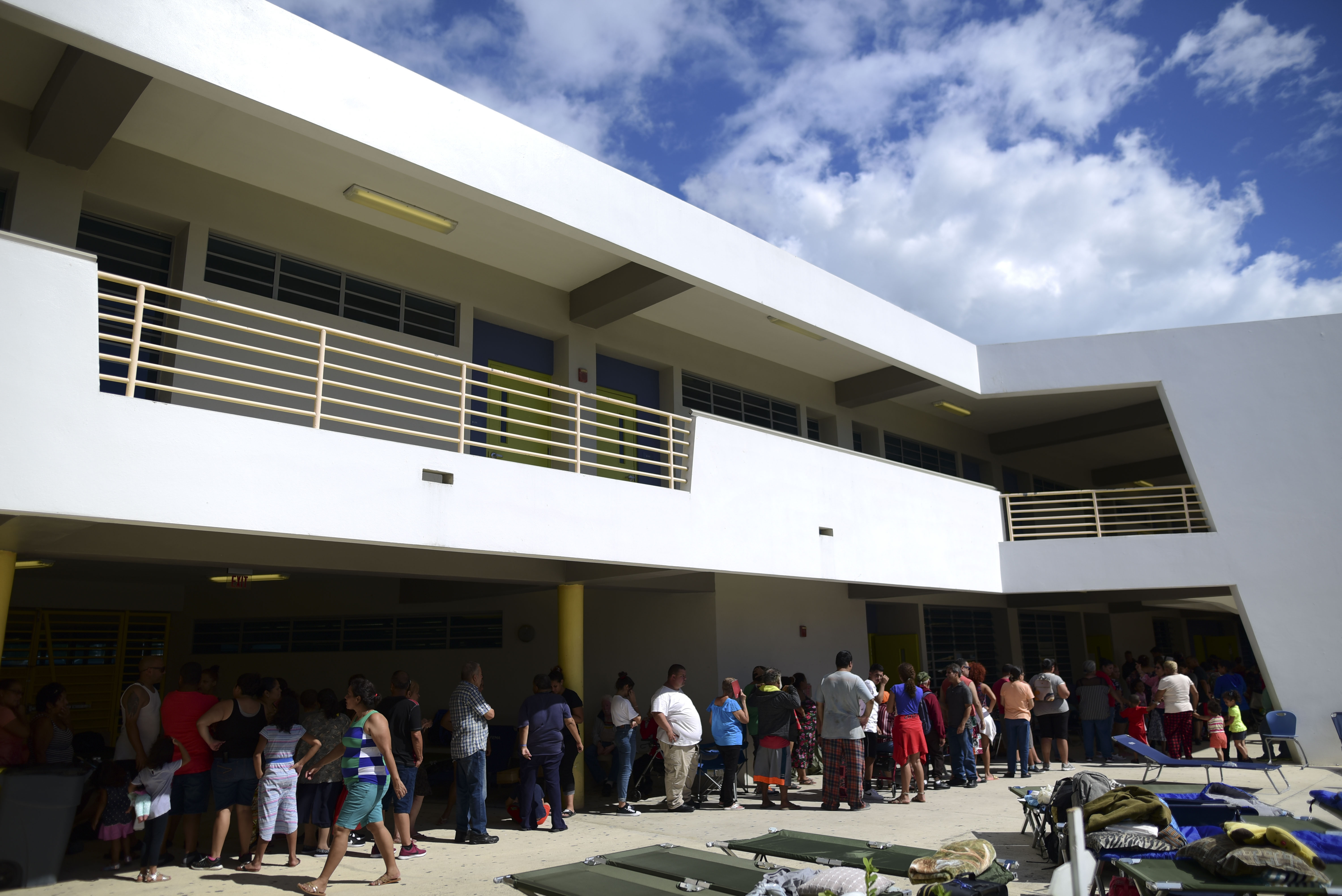 People whose homes are unsafe to enter after the previous day's magnitude 6.4 earthquake line up for lunch in an outdoor area of the Bernardino Cordero Bernard High School, which is being used as a shelter despite no electricity in Ponce, Puerto Rico on Jan. 8, 2020.