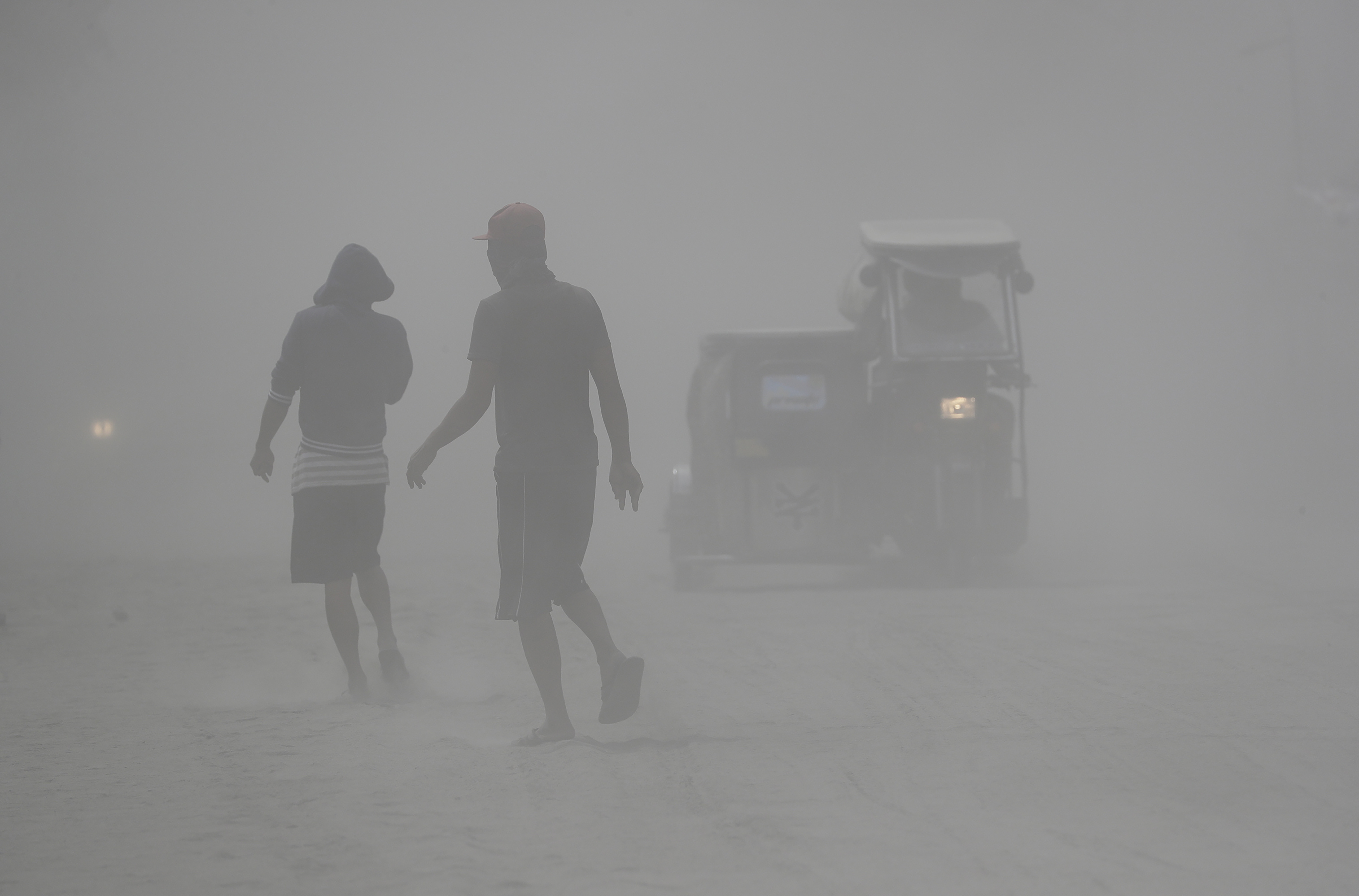 Residents walk in a cloud of ash as Taal Volcano continues to spew ash on Monday Jan. 13, 2020, in Tagaytay, Cavite province, south of Manila, Philippines. Red-hot lava gushed out of the Philippine volcano Monday after a sudden eruption of ash and steam that forced villagers to flee en masse and shut down Manila's international airport, offices and schools.