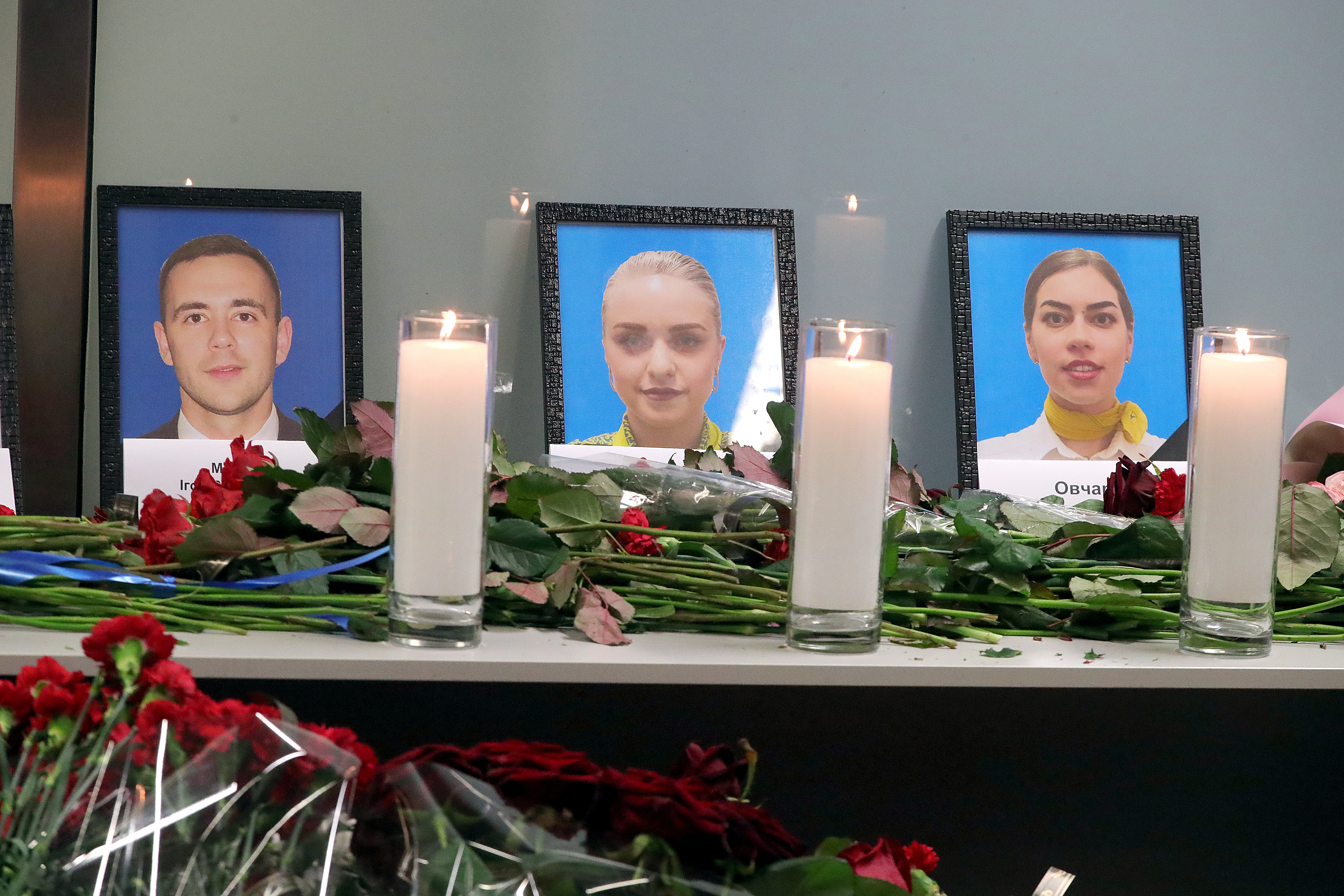 Candles and flowers are pictured at the portraits of flight attendants Ihor Matkov, Yuliia Salohub and Valeriia Ovcharuk (L to R) who were among 176 people on board of the Ukraine International Airlines Boeing 737 (PS752) killed in the Jan. 8 plane crash in Iran.