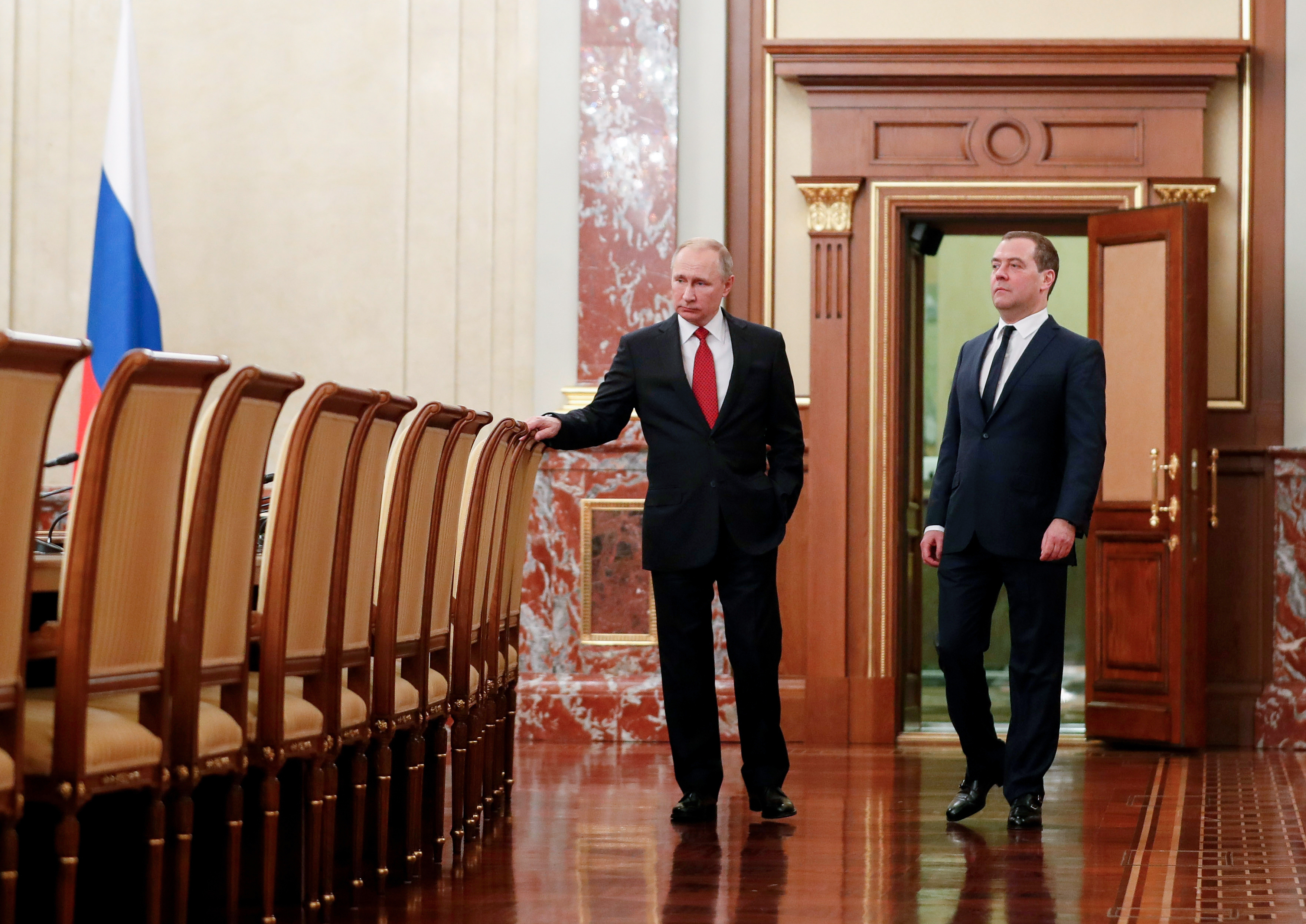 Russian President Vladimir Putin, right, and Russian Prime Minister Dmitry Medvedev talk to each other prior to a cabinet meeting in Moscow, Russia, Wednesday, Jan. 15, 2020.