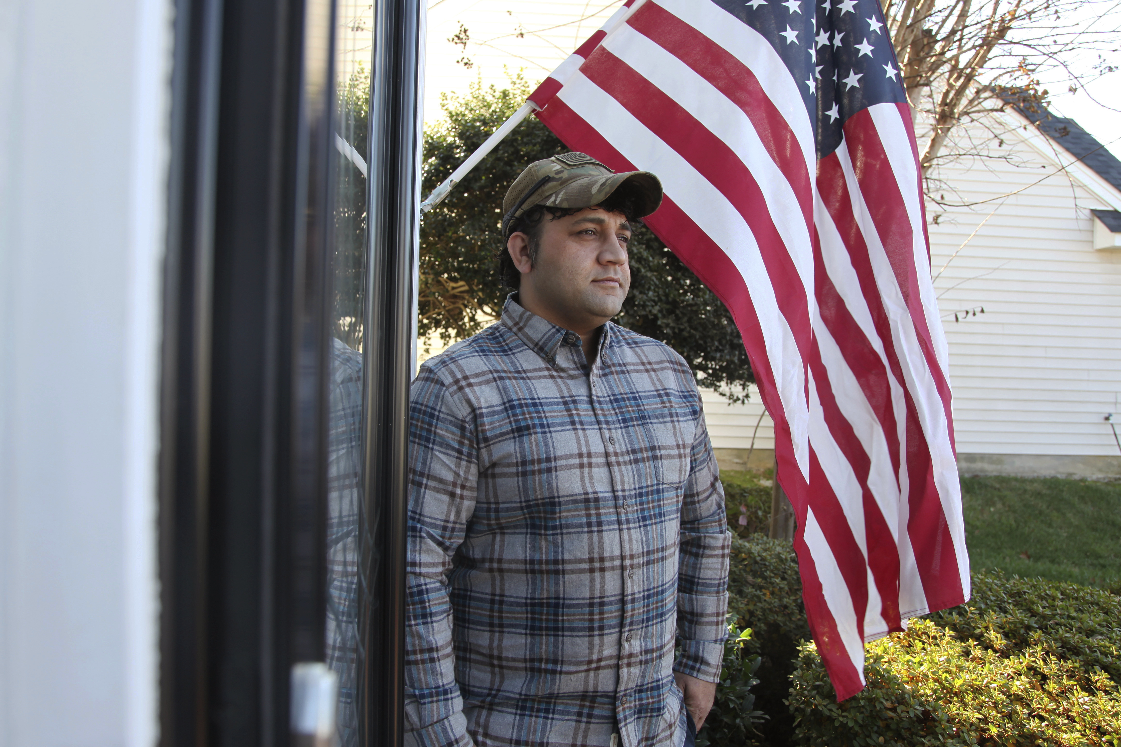 Zia Ghafoori stands beside an American flag hanging at his Charlotte, N.C., home on Dec. 16, 2019.