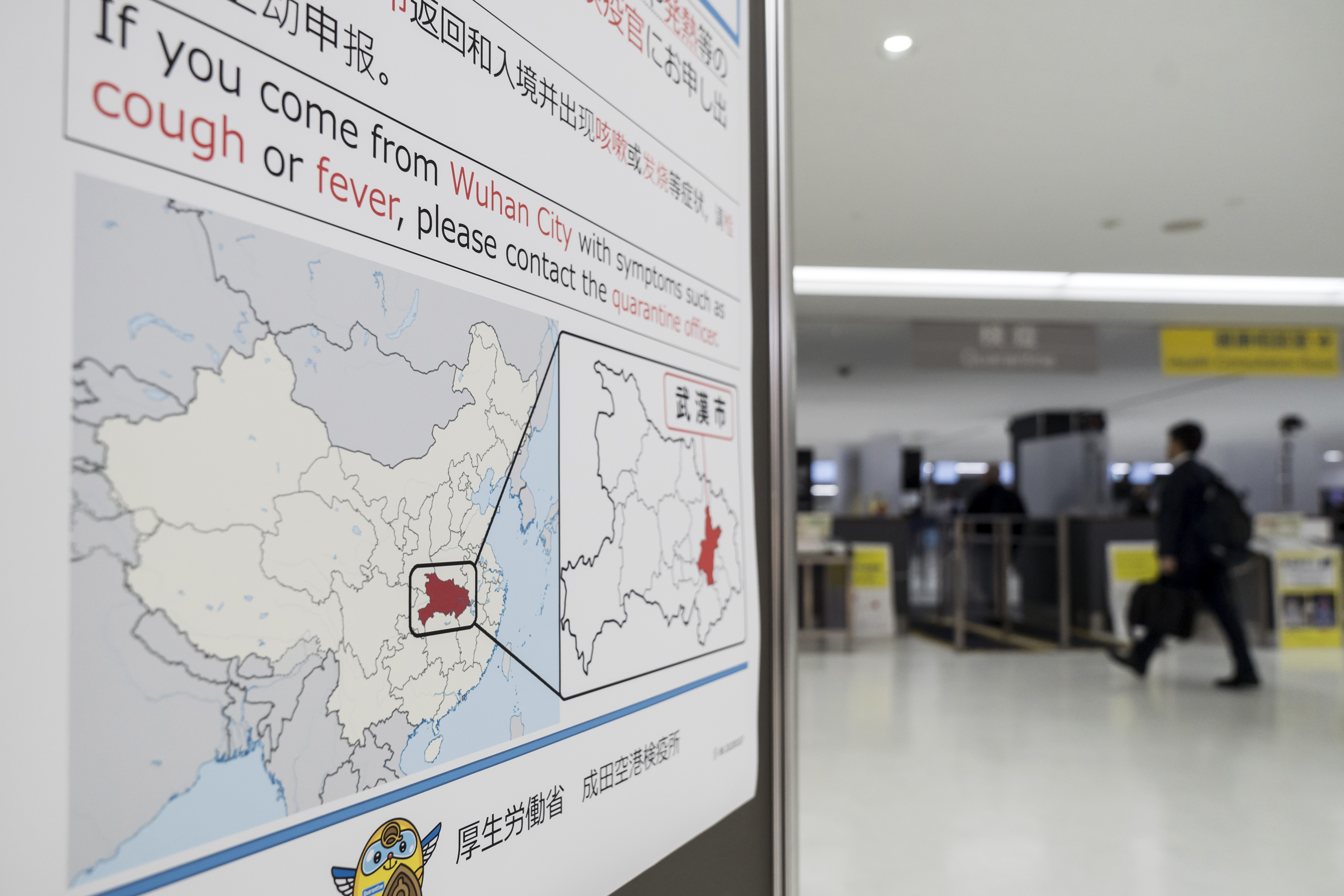 A passenger walks past a notice for  passengers from Wuhan, China displayed near a quarantine station at Narita airport on Jan. 17, 2020 in Narita, Japan.