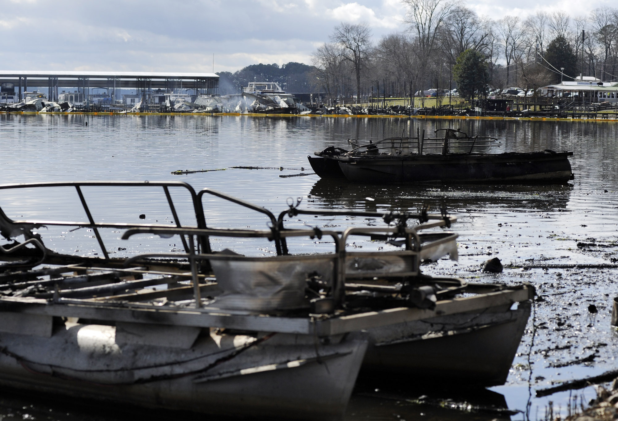 The charred remains of boats are viewed following a fire that authorities say killed at least eight people at a marina in Scottsboro, Ala., on Jan. 27, 2020.