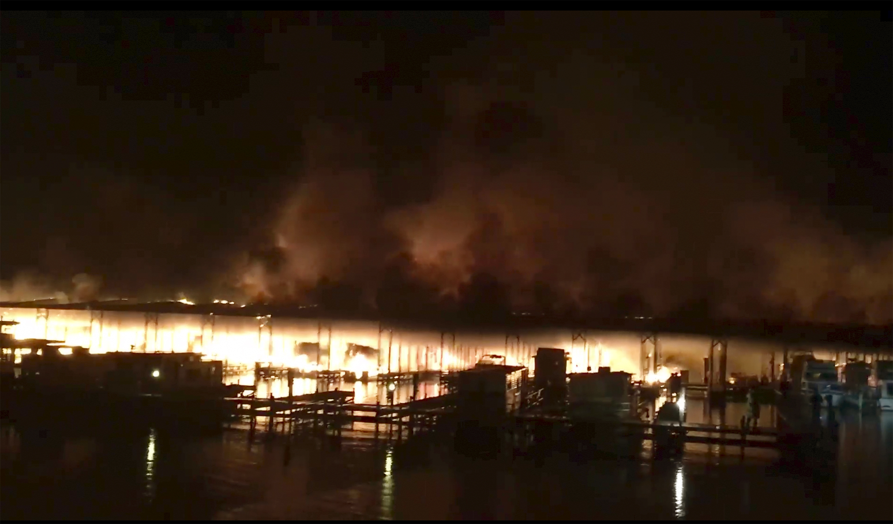 Fire burning on a dock where at least 35 vessels, many of them houseboats, were destroyed early  Jan. 27, 2020, in Scottsboro, Ala. Scottsboro Fire Chief Gene Necklaus is confirming fatalities following the blaze.