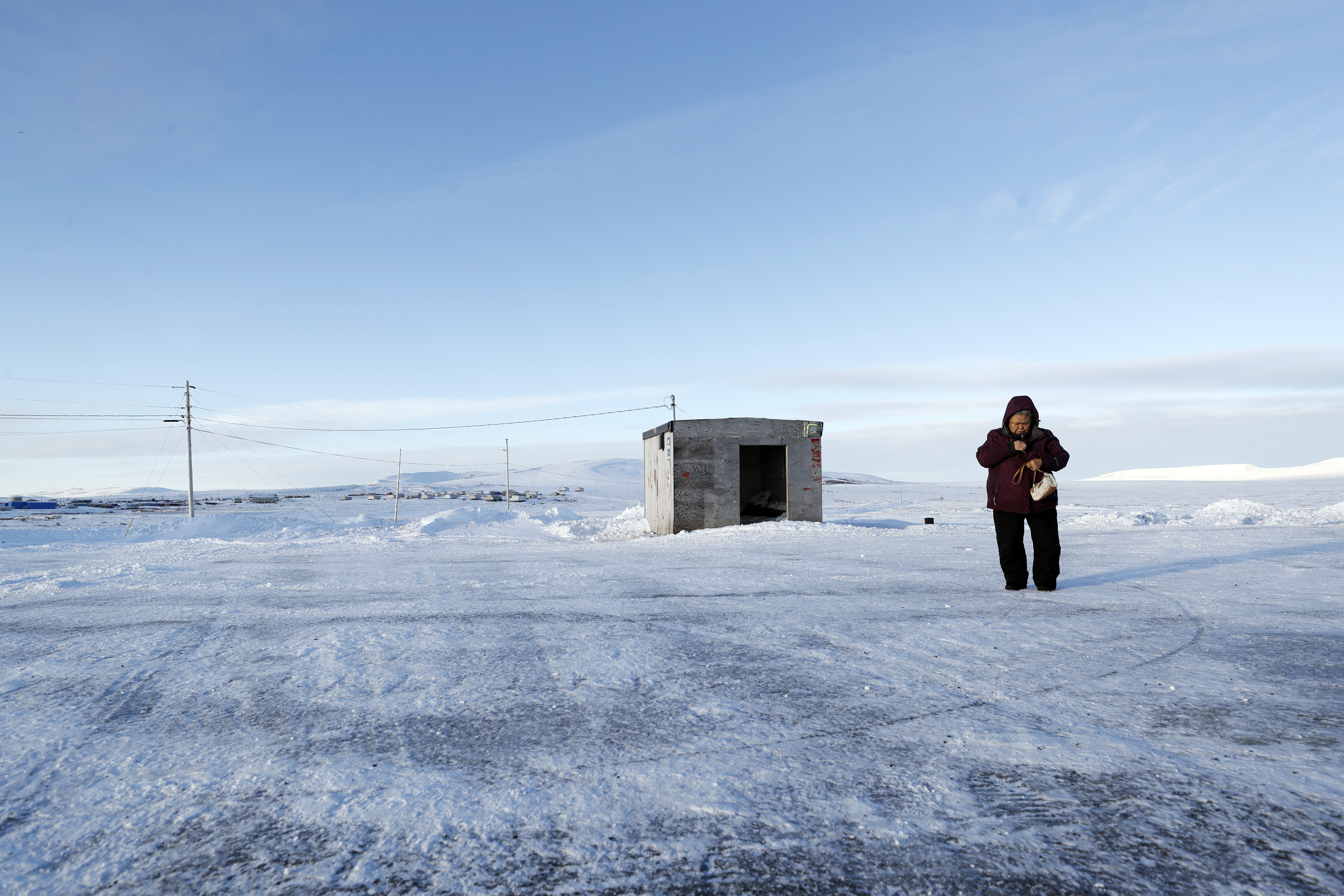 In thisJan. 18, 2020, photo, a woman bundles up against the cold, in Toksook Bay, Alaska.