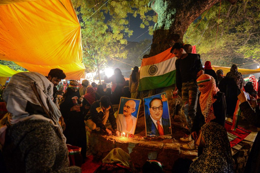 Protesters light candles near posters of Mahatma Gandhi and Bhimrao Ramji Ambedkar during a demonstration against India's new citizenship law in Allahabad (formally known as Prayagraj) on January 14, 2020.
