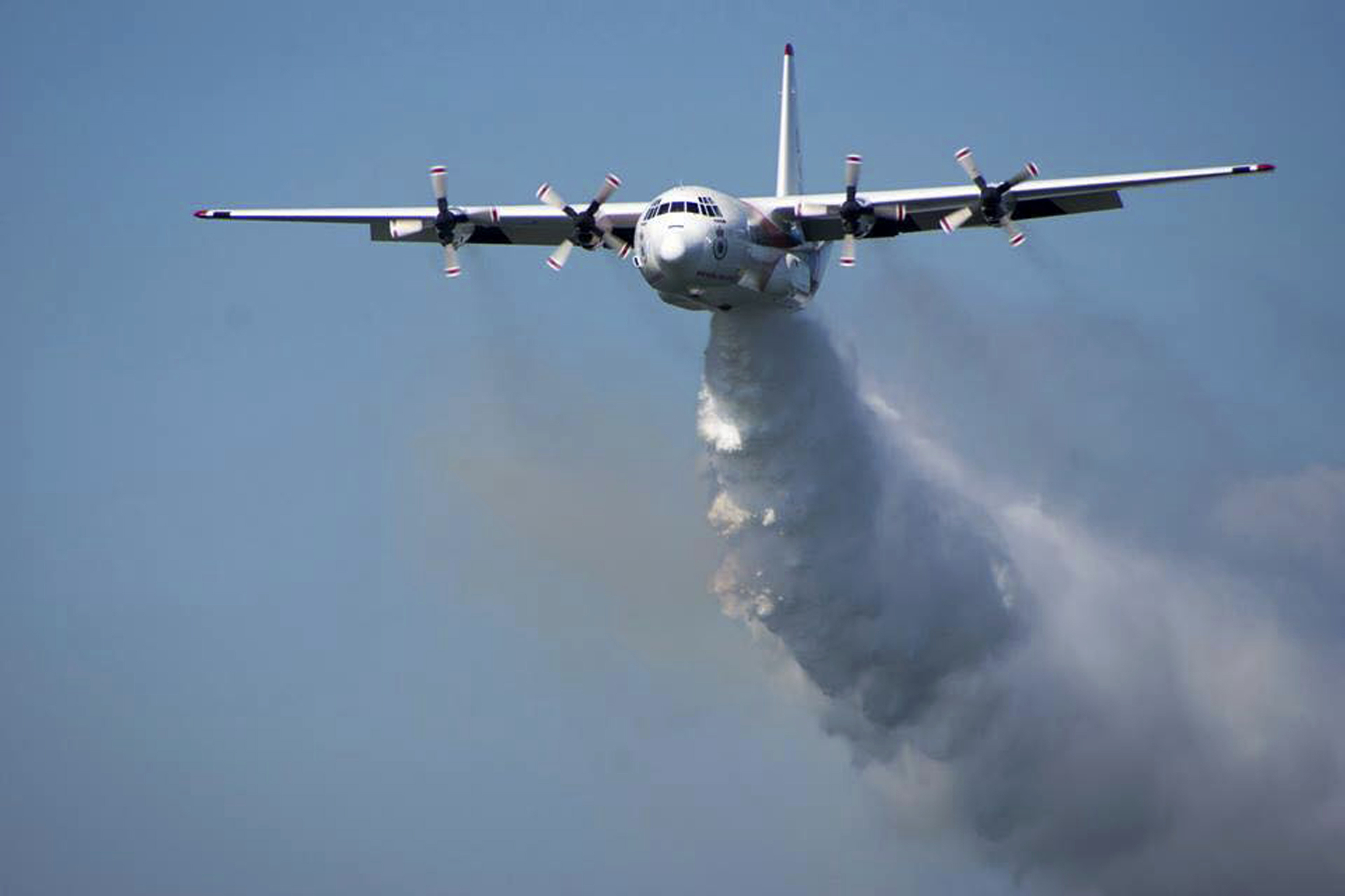 In this undated photo released from the Rural Fire Service, a C-130 Hercules plane called  Thor  drops water during a flight in Australia.