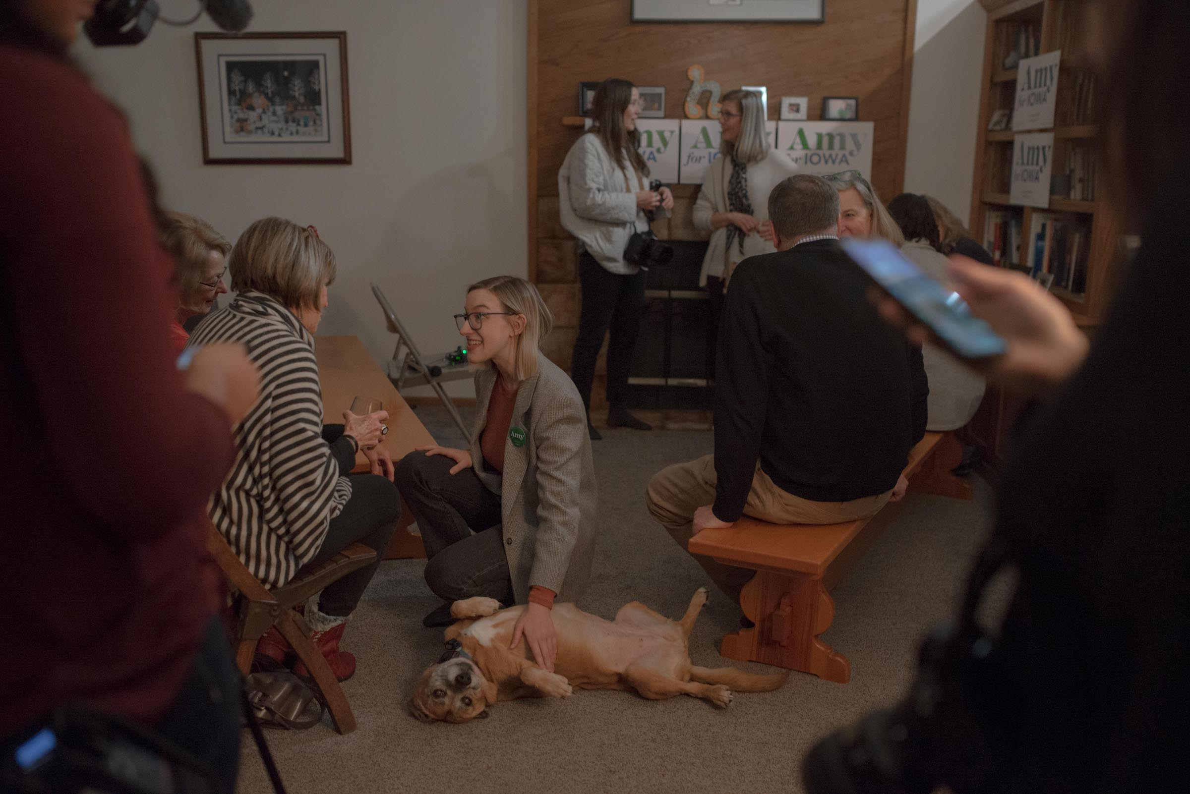Abigail Bessler pets a dog while speaking with supporters at a Hotdish House Party.