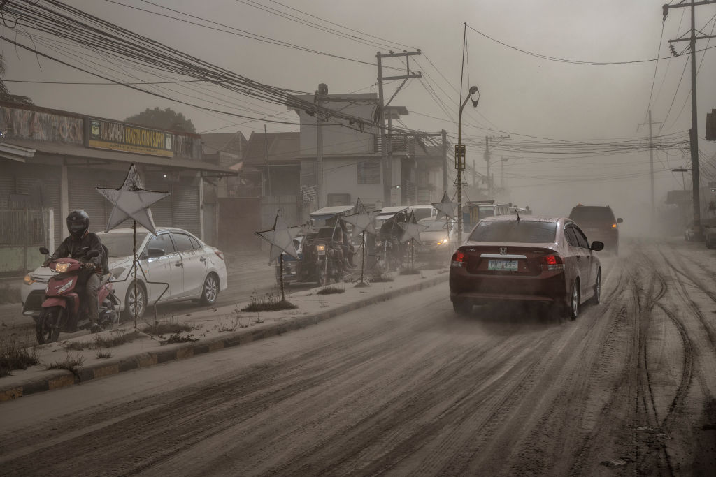 Motorists drive through a road covered in volcanic ash from Taal Volcano's eruption in Lemery, Batangas province, Philippines on Jan. 13, 2020.