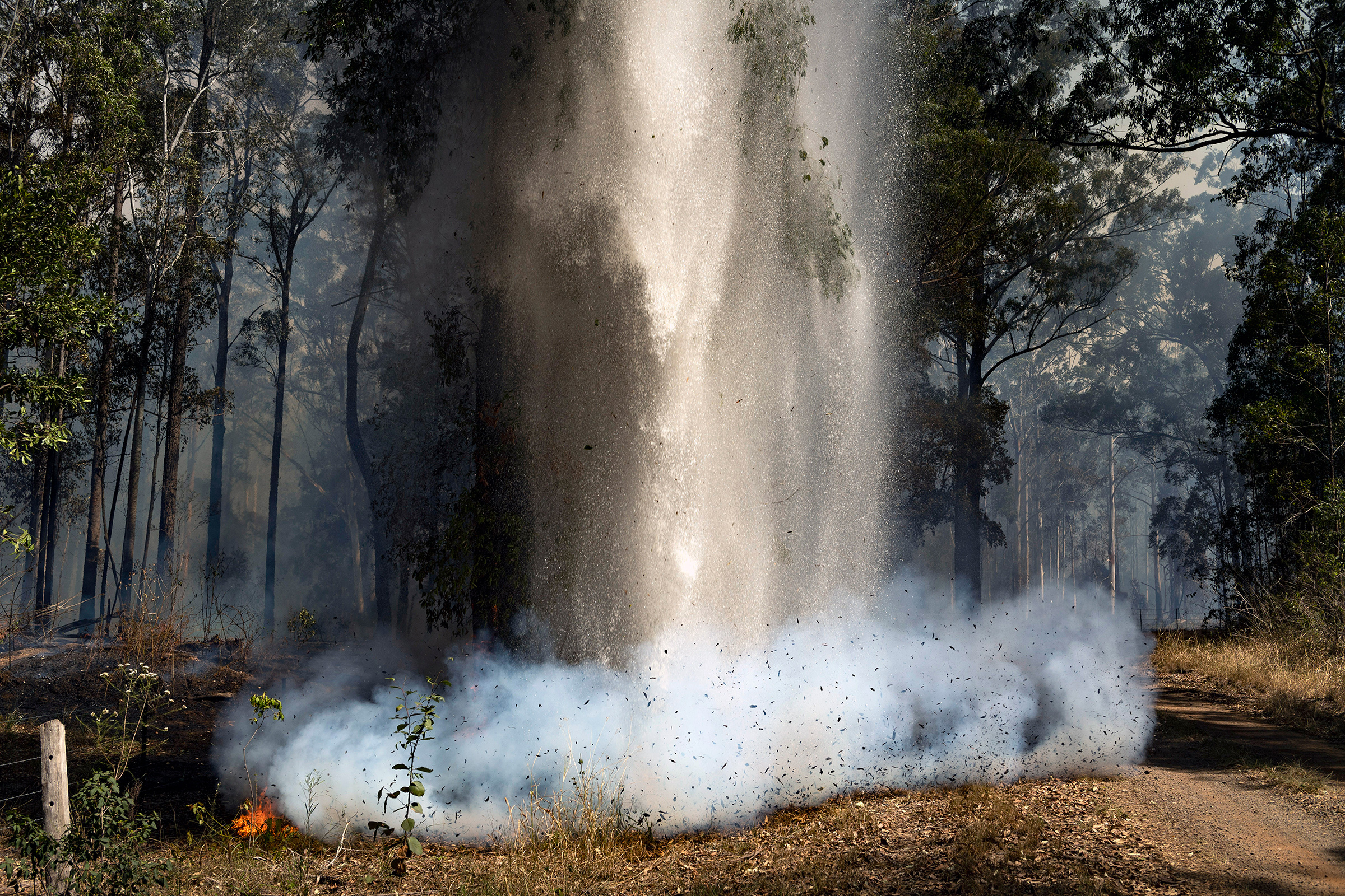 Water is dumped from a helicopter on a small fire in Hillville, New South Wales, on Nov. 12, 2019.