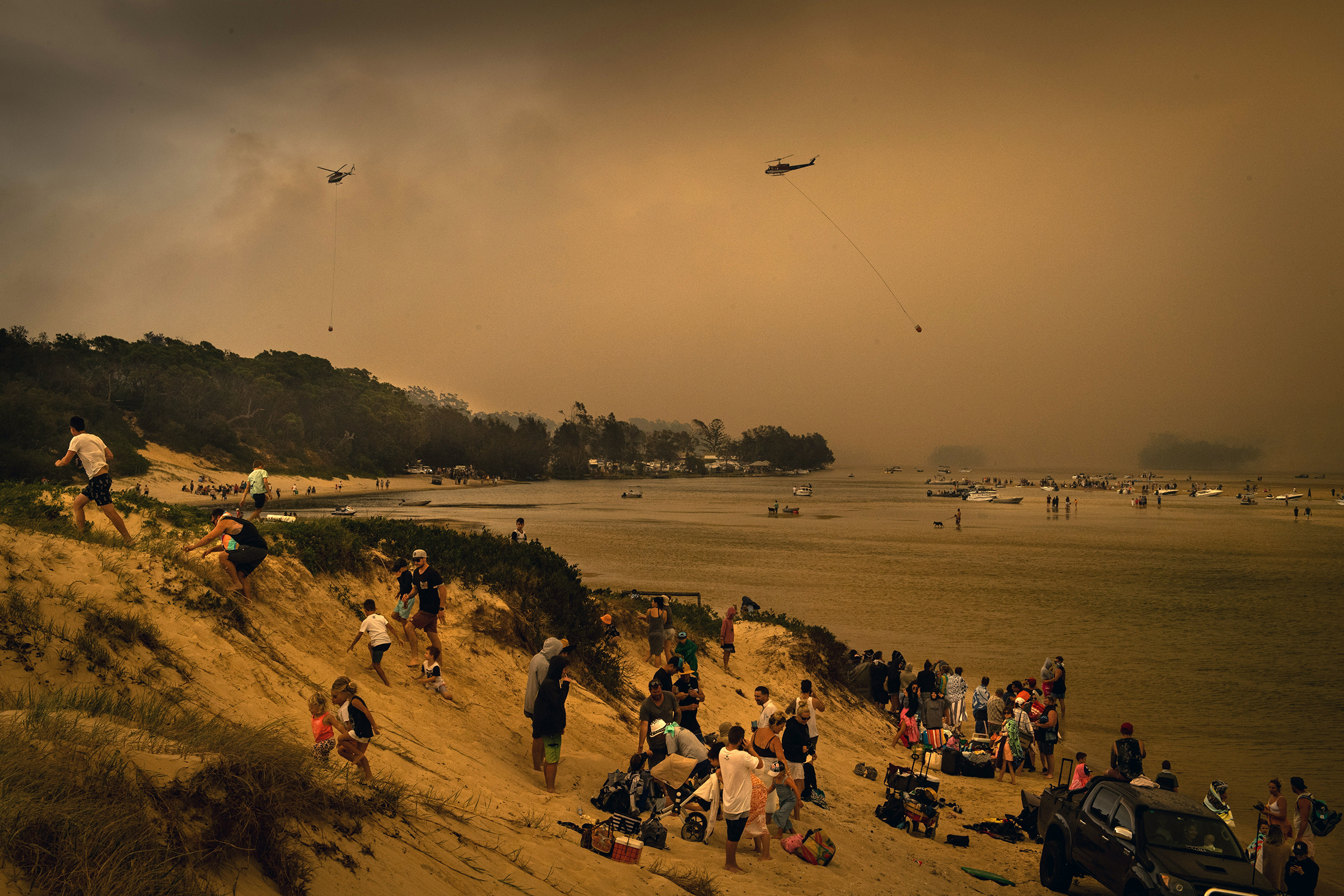 Tourists in Lake Conjola, a popular holiday destination in Australia, take refuge from wildfires on a beach from wildfires on Dec. 31, 2019.