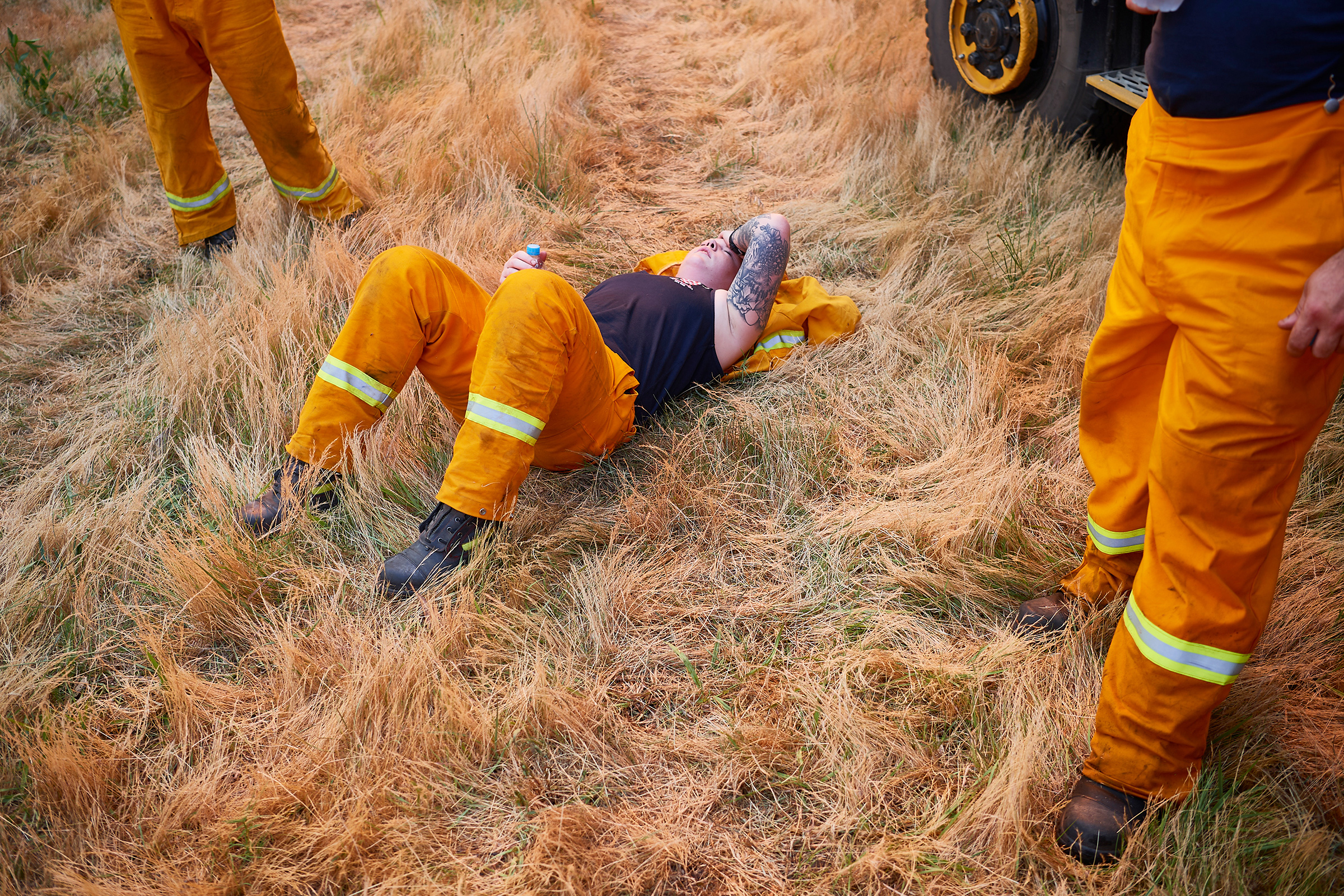 A Country Fire Authority crew member rests after a day of maintaining controlled back burns in St Albans on Nov. 21, 2019.