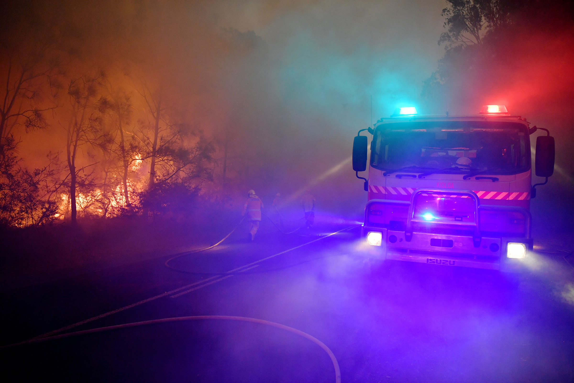 Fire and rescue officers try to contain a bushfire near Kioloa, New South Wales, on Dec. 3, 2019.