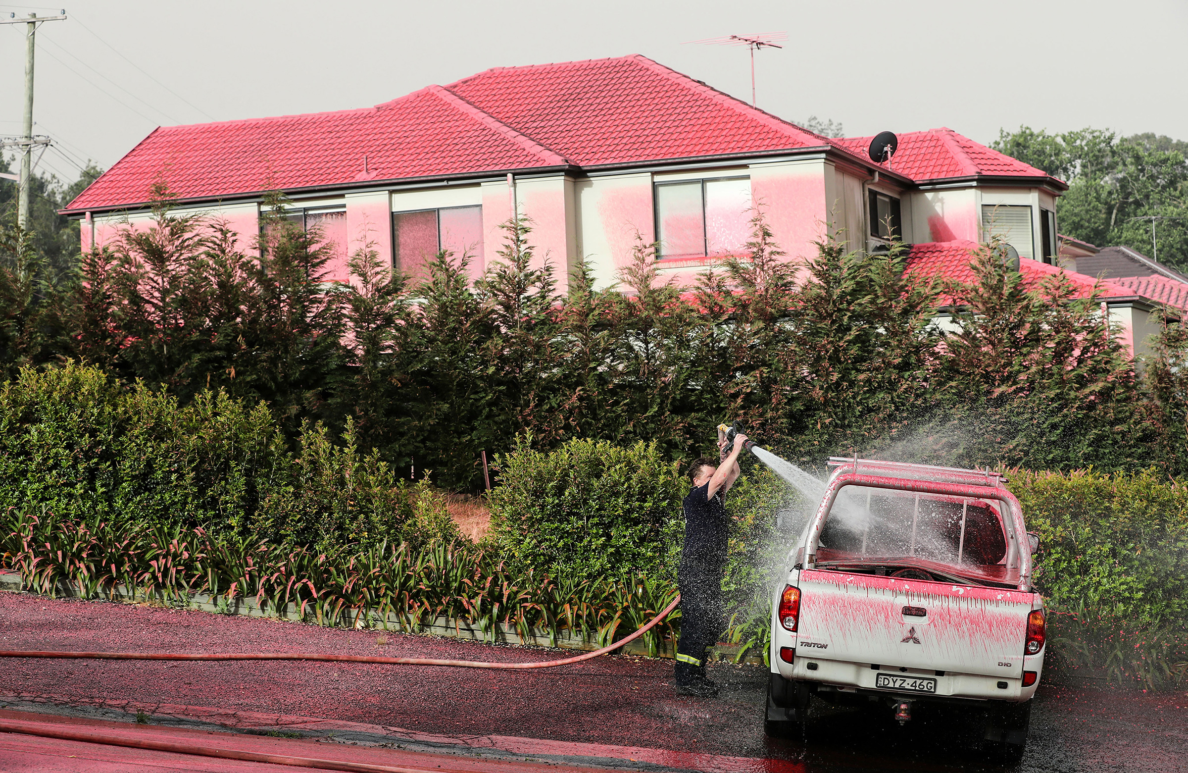 A firefighter washes a truck covered by pink fire retardant in South Turramurra, New South Wales, on Nov. 12, 2019.