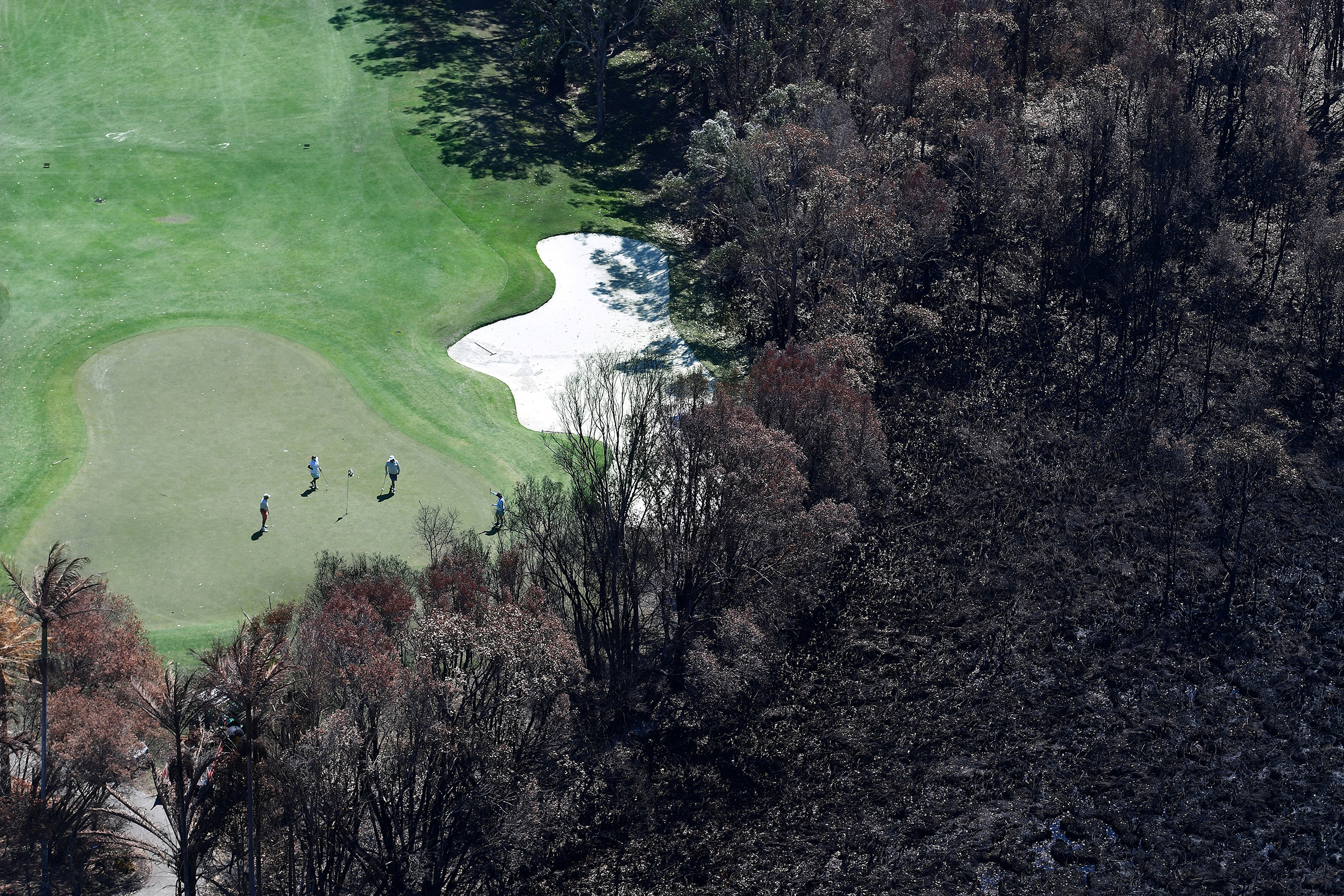 Golfers on the green next to a bushfire-damaged area in Peregian Beach, on the Sunshine Coast, on Sept. 10, 2019.