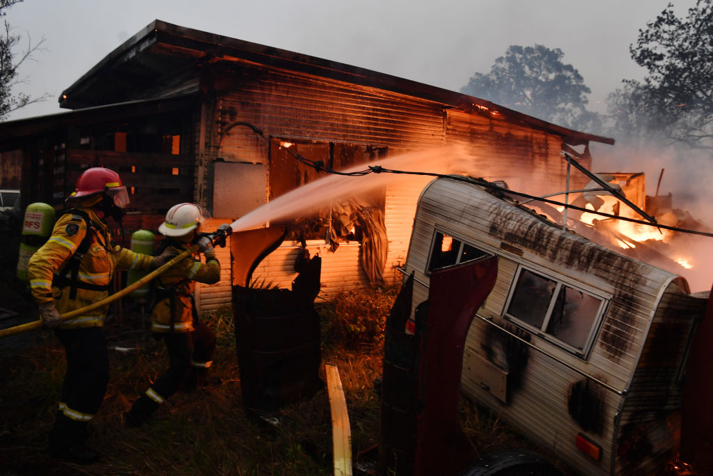 Rural Fire Service firefighters extinguish a fire on a property in Moruya, Australia on Jan. 23, 2020.