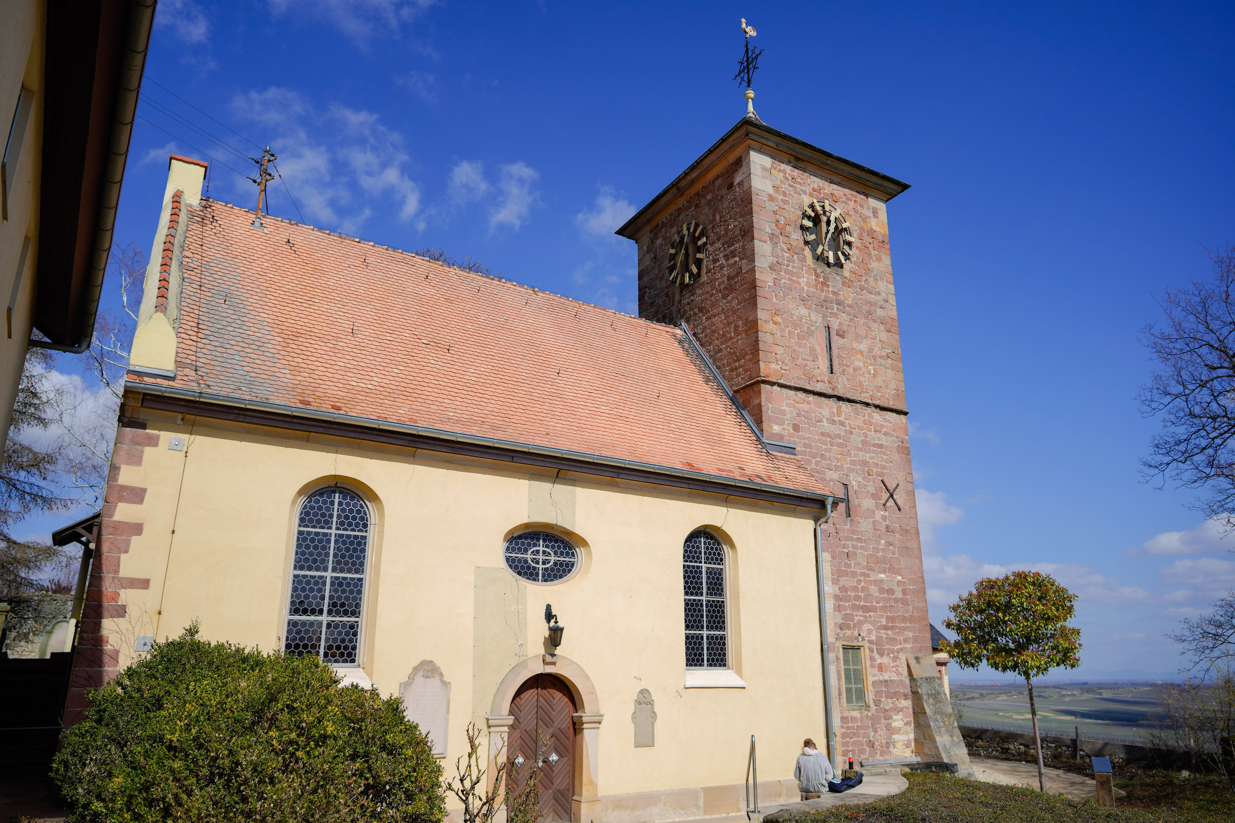 The Protestant Church in Herxheim am Berg, in front of which an information board had recently been erected, on March 19, 2019. The plaque explains how the bell with the inscription  Everything for the Fatherland. Adolf Hitler  had entered the church and that it would remain there as a reminder for the future.