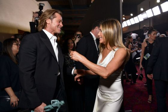 Brad Pitt grabs Jennifer Aniston's right hand, as the two face each other smiling. Pitt has the trophy he won in his right hand, while Aniston's left hand is raised.