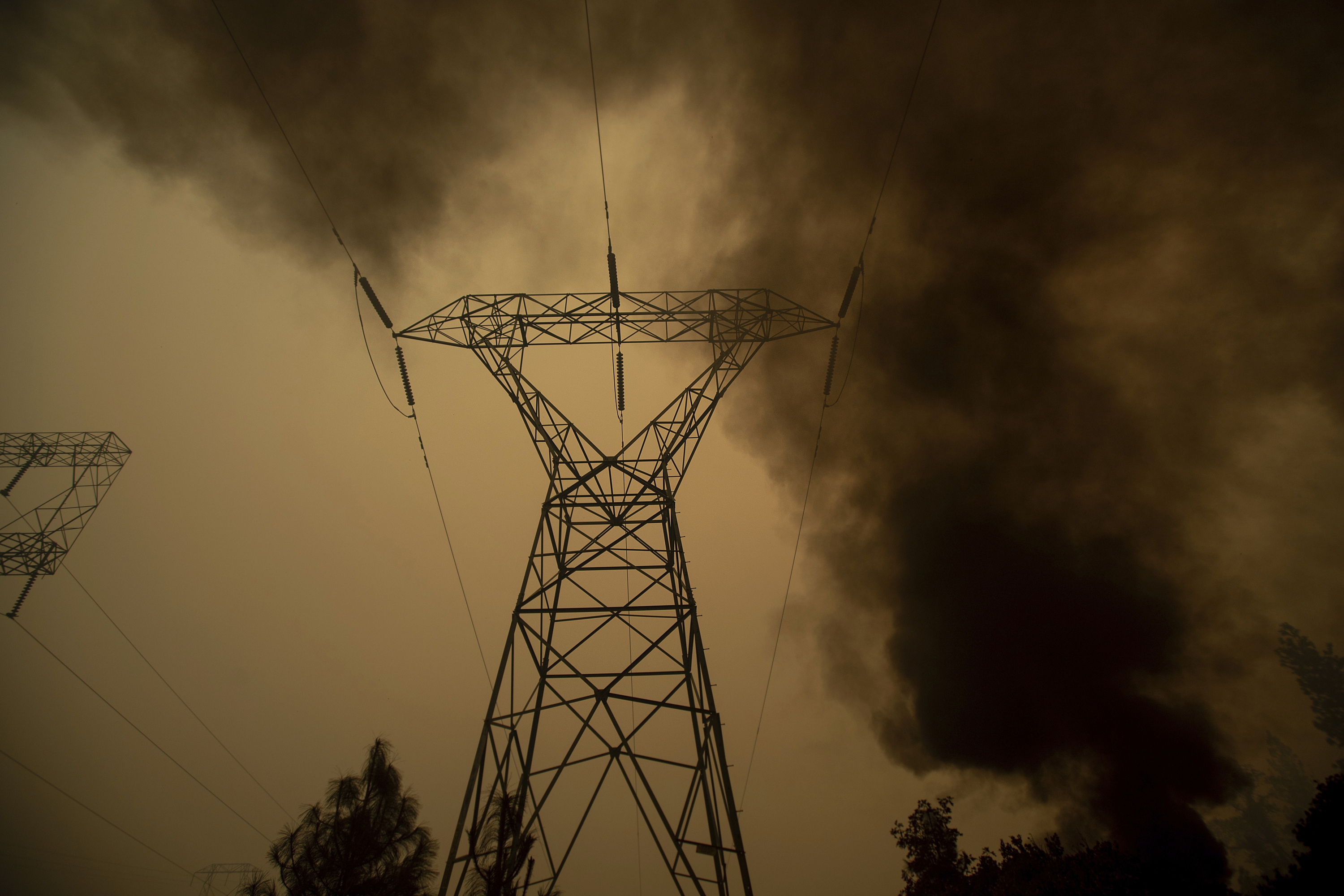 Smoke billows around power transmission lines as the Camp Fire burns in Big Bend, Calif. on Nov. 9, 2018.