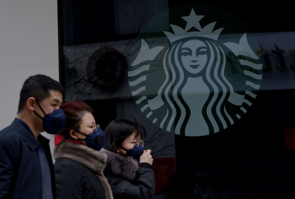 People wearing protective face masks walk past a closed Starbucks coffee shop at a grocery in Beijing on Jan. 29, 2020.