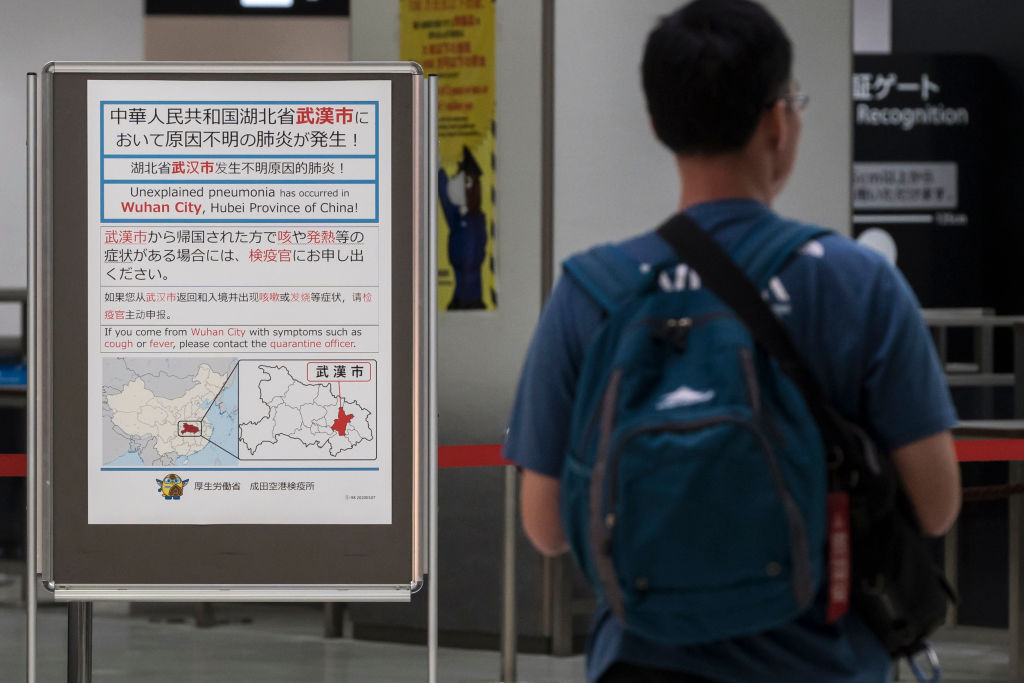 A passenger walks past a notice for  passengers from Wuhan, China displayed near a quarantine station at Narita airport on January 17, 2020 in Narita, Japan.