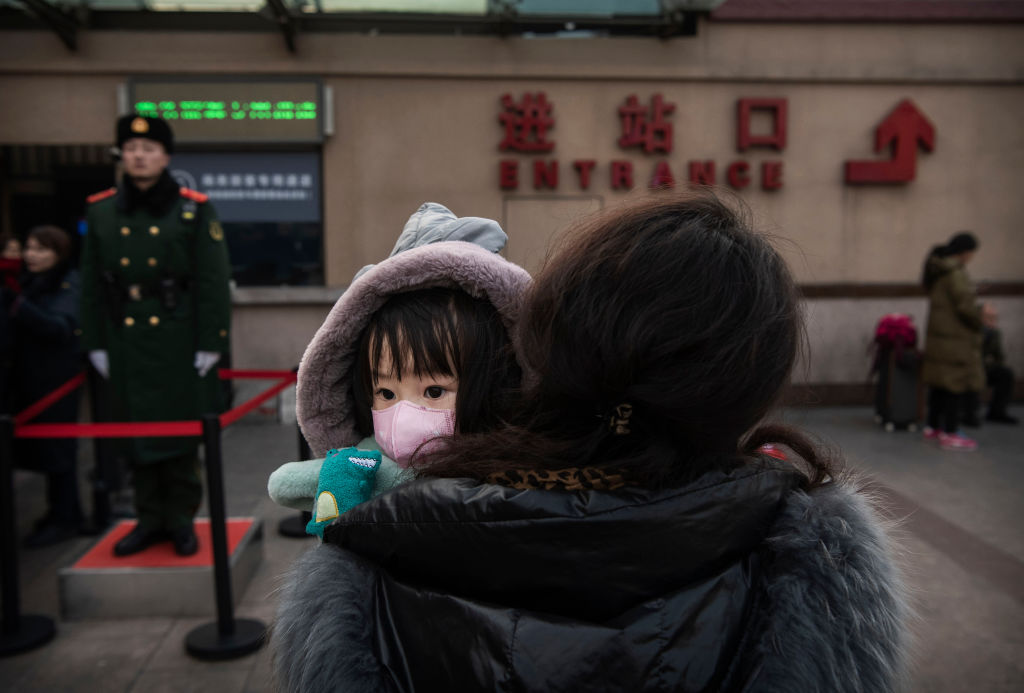 A girl wears a protective mask as she and a relative wait to board a train at Beijing Railway Station on Jan. 21, 2020.