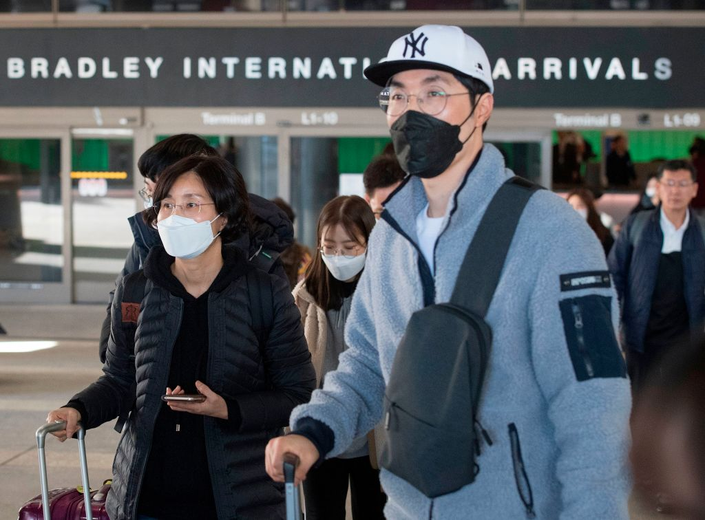 Passengers wear masks to protect against the spread of coronavirus as they arrive on a flight from Asia at the Los Angeles International Airport on Jan. 29, 2020.