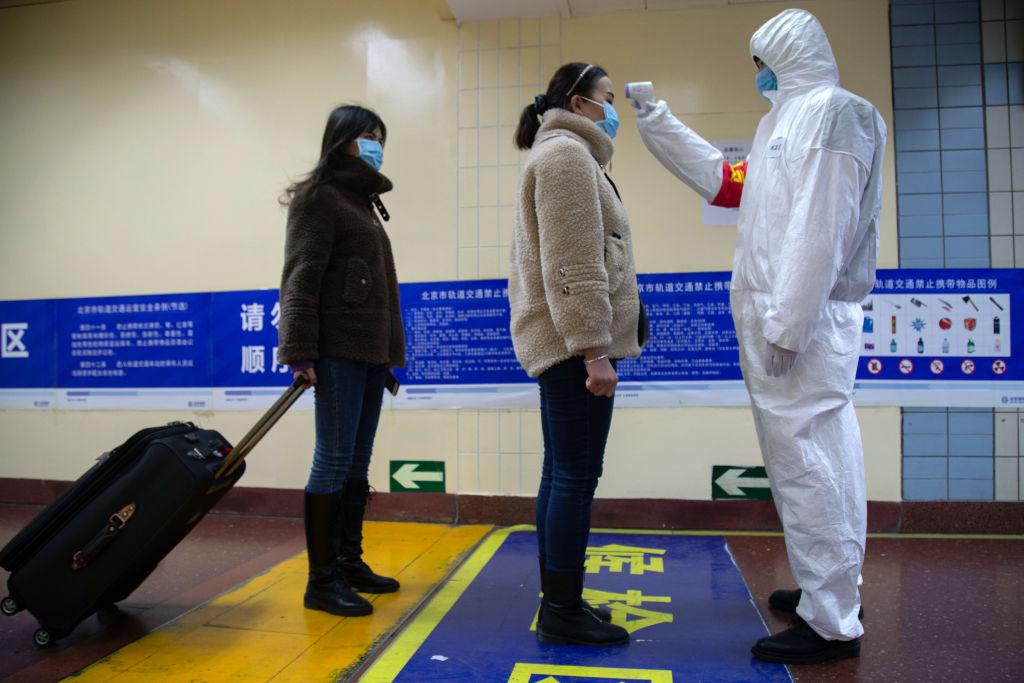 A health worker checks the temperature of women entering the subway in Beijing, China on Jan. 26, 2020.