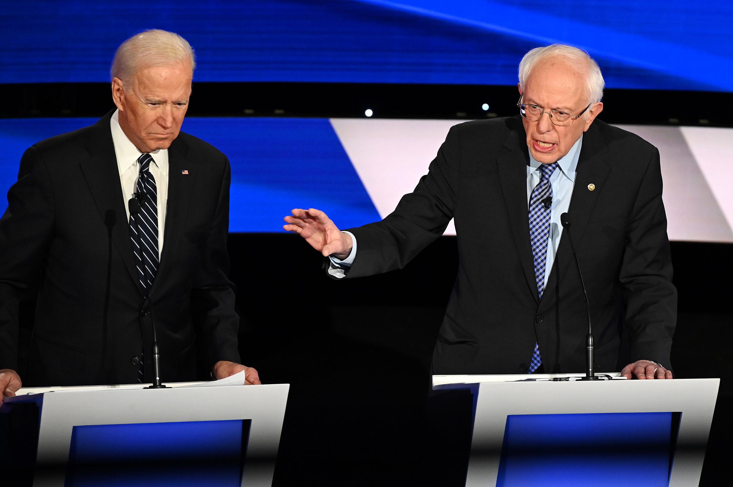 (L-R) Democratic presidential hopefuls Former Vice President Joe Biden (L) and Vermont Senator Bernie Sanders participate in the seventh Democratic primary debate of the 2020 presidential campaign in Des Moines, Iowa on Jan. 14, 2020.