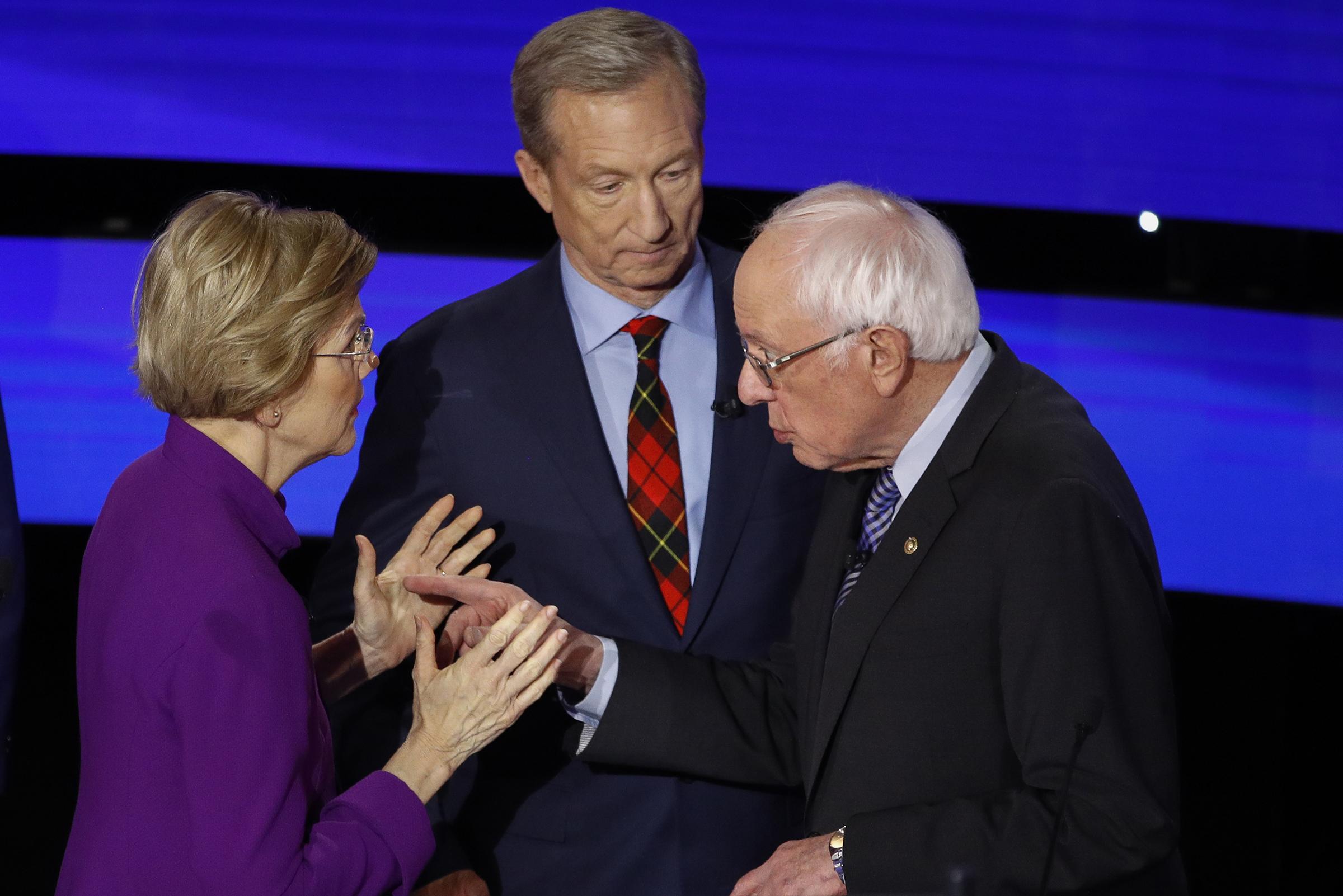 Democratic presidential candidate Sen. Elizabeth Warren, D-Mass., left and Sen. Bernie Sanders, I-Vt., talk after a Democratic presidential primary debate in Des Moines, Iowa., as businessman Tom Steyer looks on, on Jan. 14, 2020.