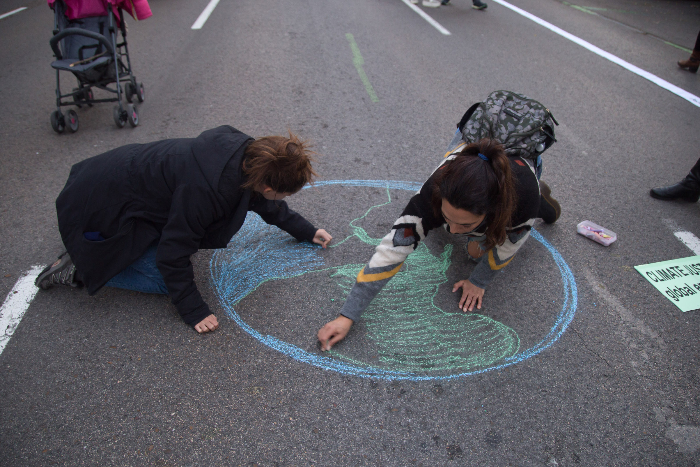 Activists draw the planet earth on the ground during a demonstration in Madrid during COP25, on Dec. 6, 2019.