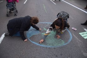 Activists draw the planet earth on the ground during the