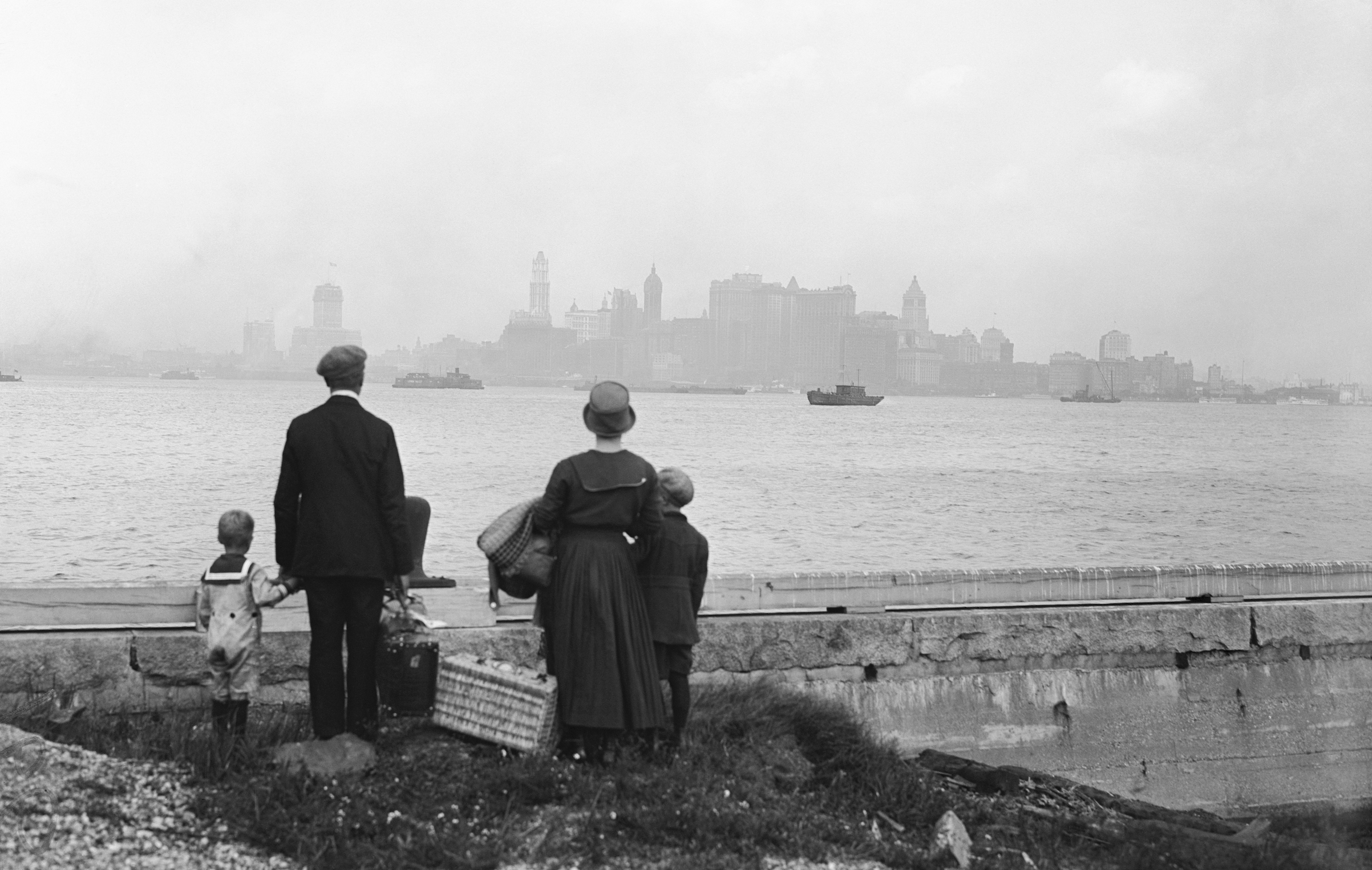 An immigrant family on the dock at Ellis Island, N.Y., looking at New York's skyline while awaiting the ferry to take them there, in 1925.
