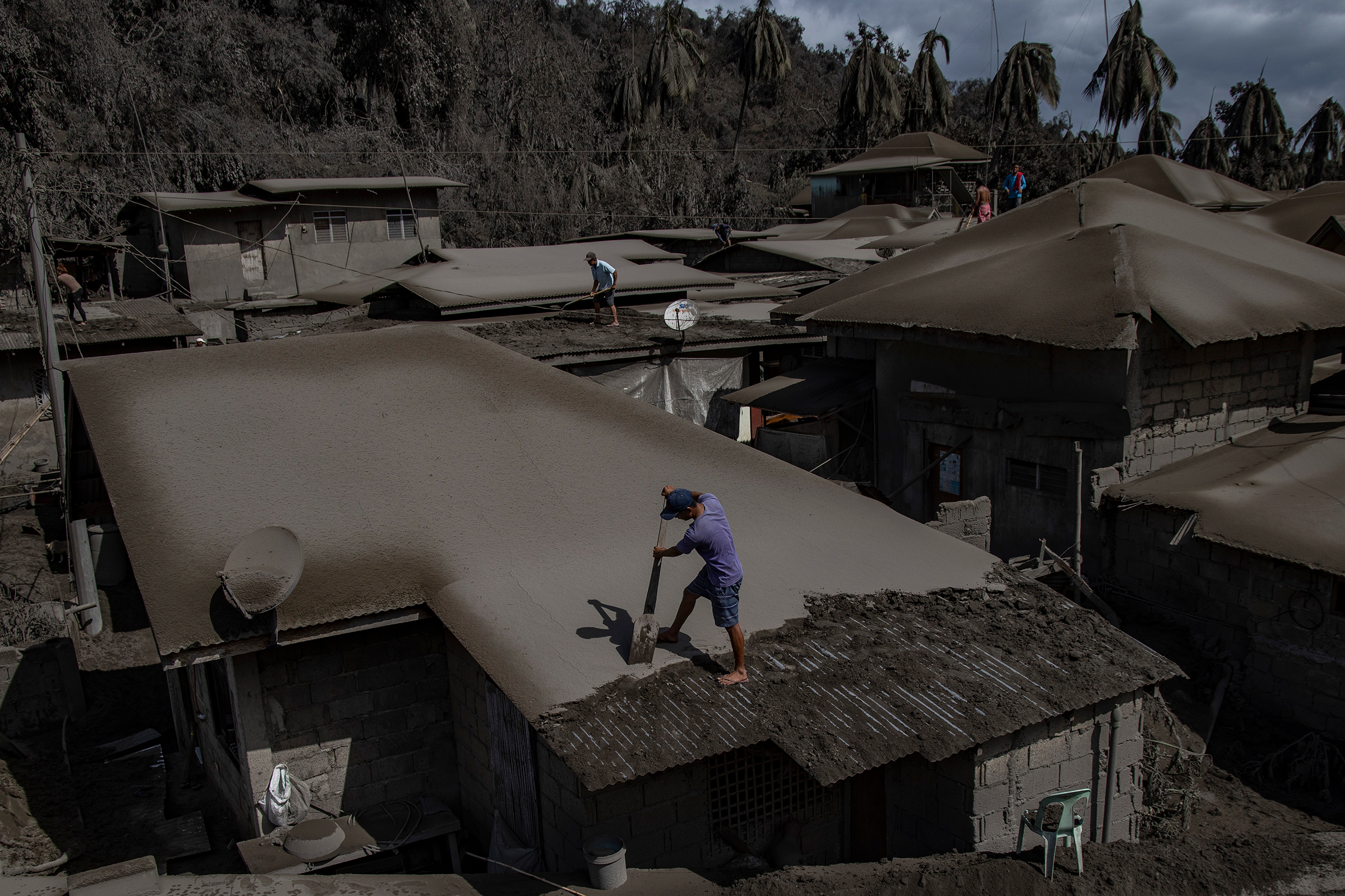Men clean rooftops of ash from the recent eruption.
