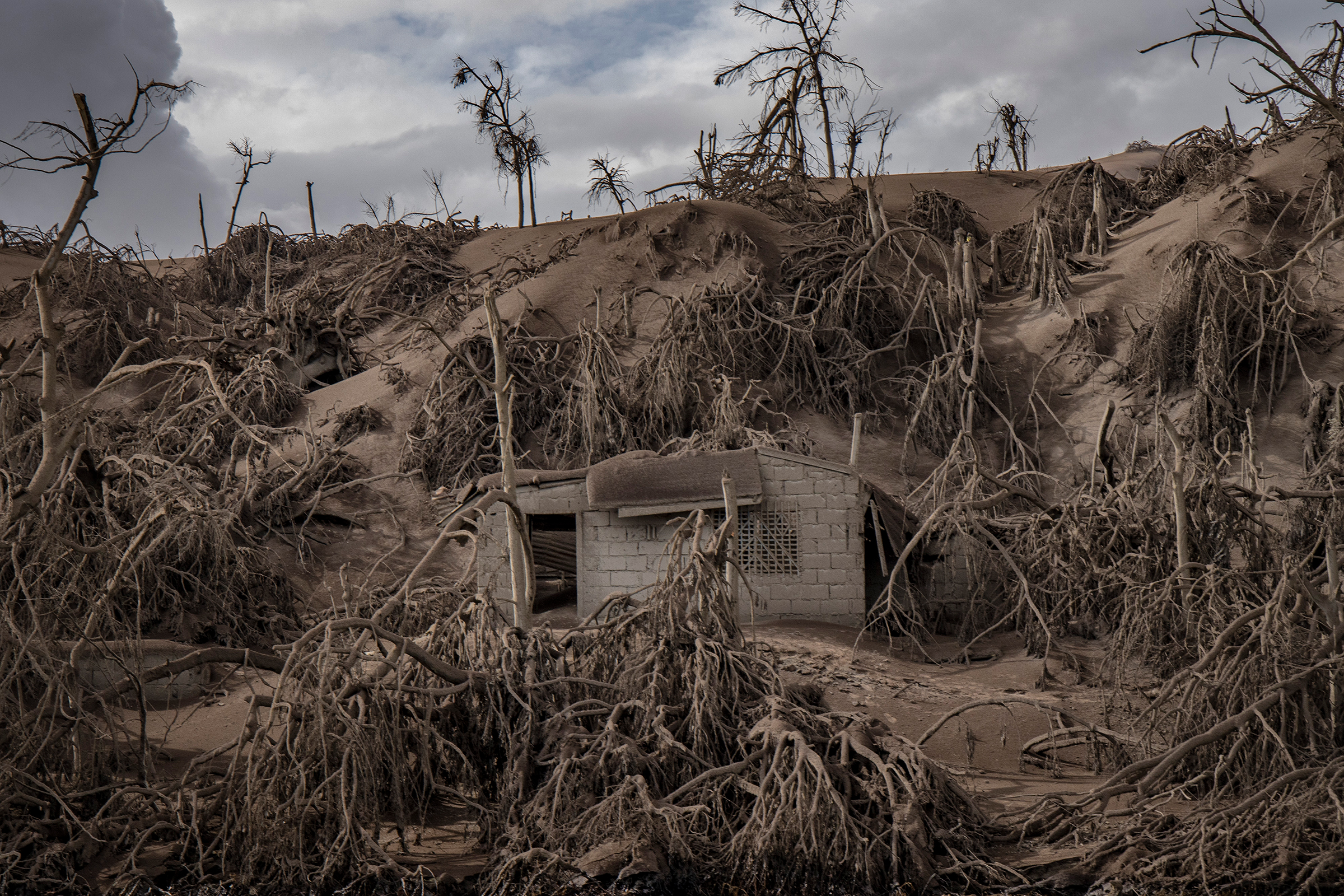 A house near the crater is buried in ash.