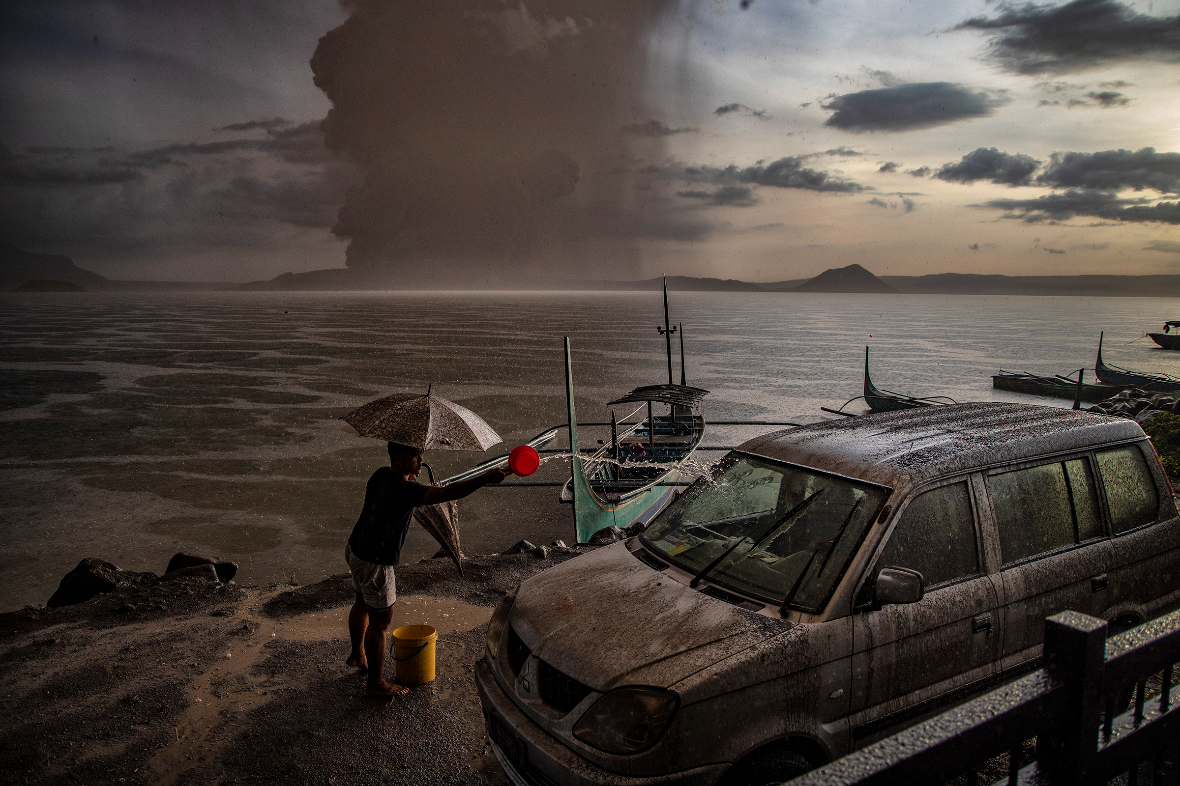 A resident in Talisay, in Batangas province, splashes water on a vehicle covered in ash mixed with rainwater as the Taal Volcano erupts on Jan. 12.