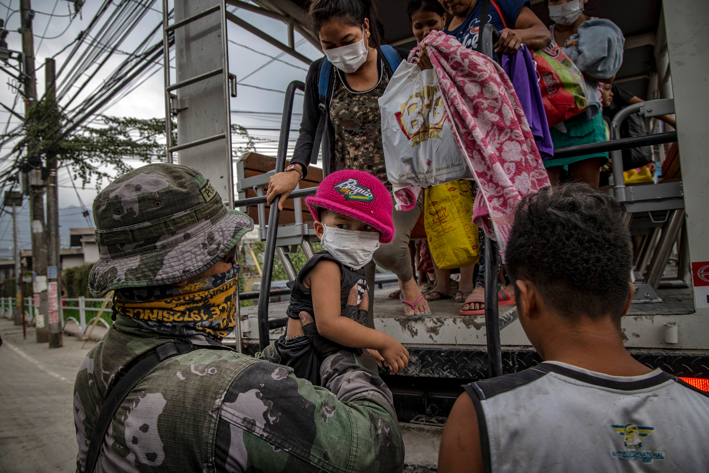Residents fleeing the eruption arrive to an evacuation center in Santo Thomas on Jan. 13.