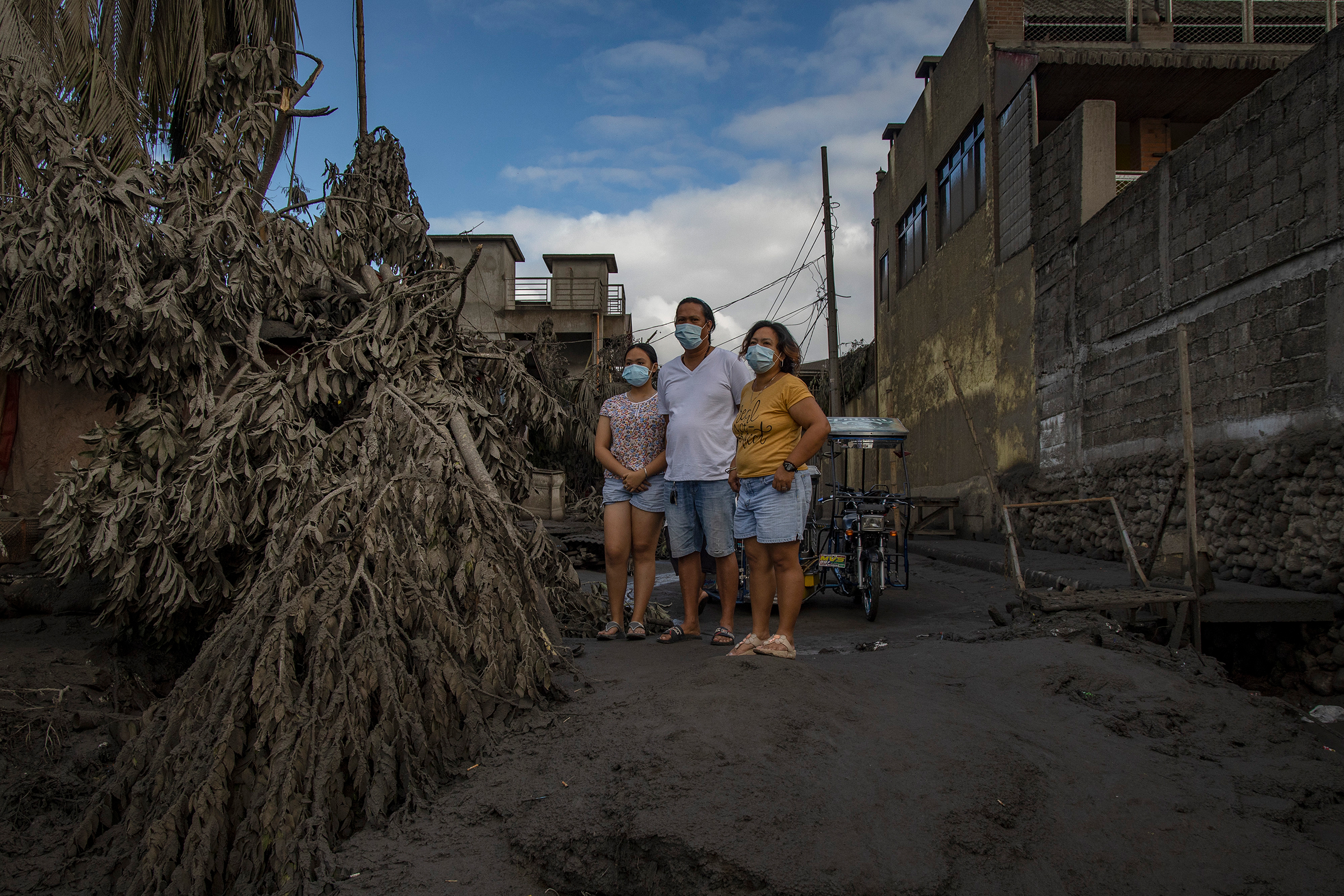 Residents return to their homes covered in ash in Talisay on Jan. 14.