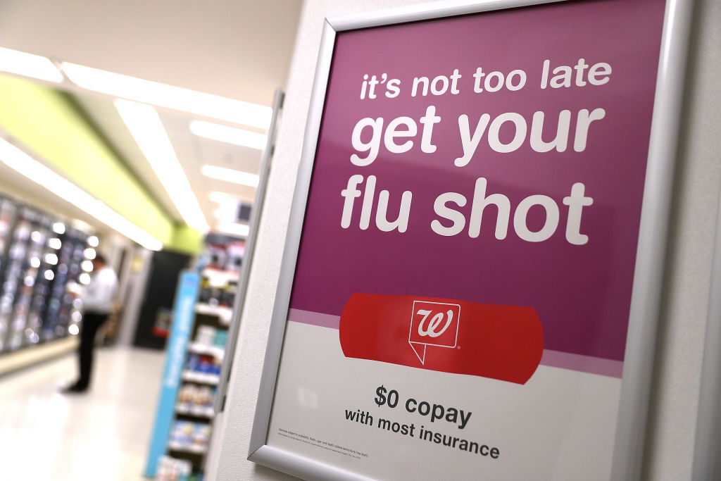 A sign advertising flu shots is displayed at a Walgreens pharmacy in San Francisco, Calif., on Jan. 22, 2018.