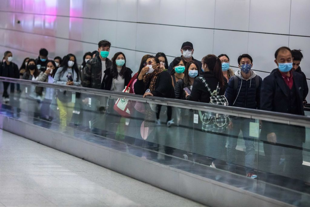 People wearing facemasks ride a travelator inside a train station on the second day of the Lunar New Year of the Rat in Hong Kong on Jan. 26, 2020.