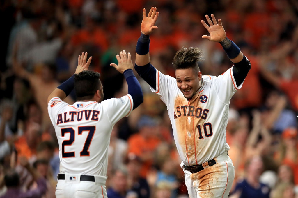 Yuli Gurriel #10 of the Houston Astros celebrates with teammate Jose Altuve #27 after scoring off of a double hit by Brian McCann #16 against Tommy Kahnle #48 of the New York Yankees during the fifth inning in Game Seven of the American League Championship Series at Minute Maid Park on October 21, 2017 in Houston, Texas.