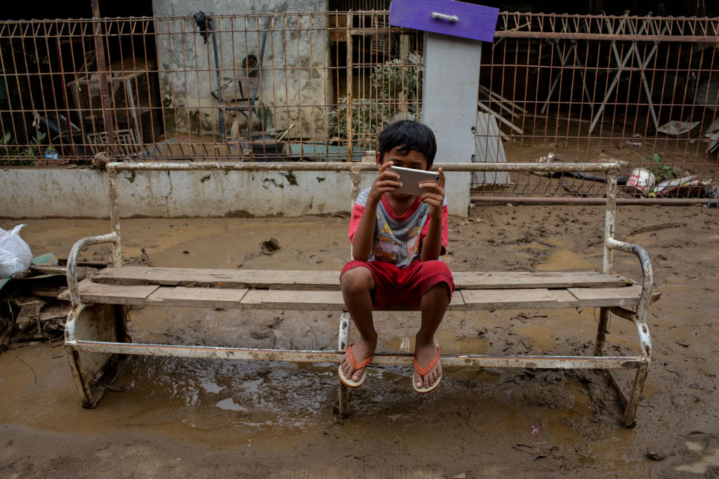 A boy plays on a phone after the flood in Bekasi, Indonesia, on Jan. 3, 2020.