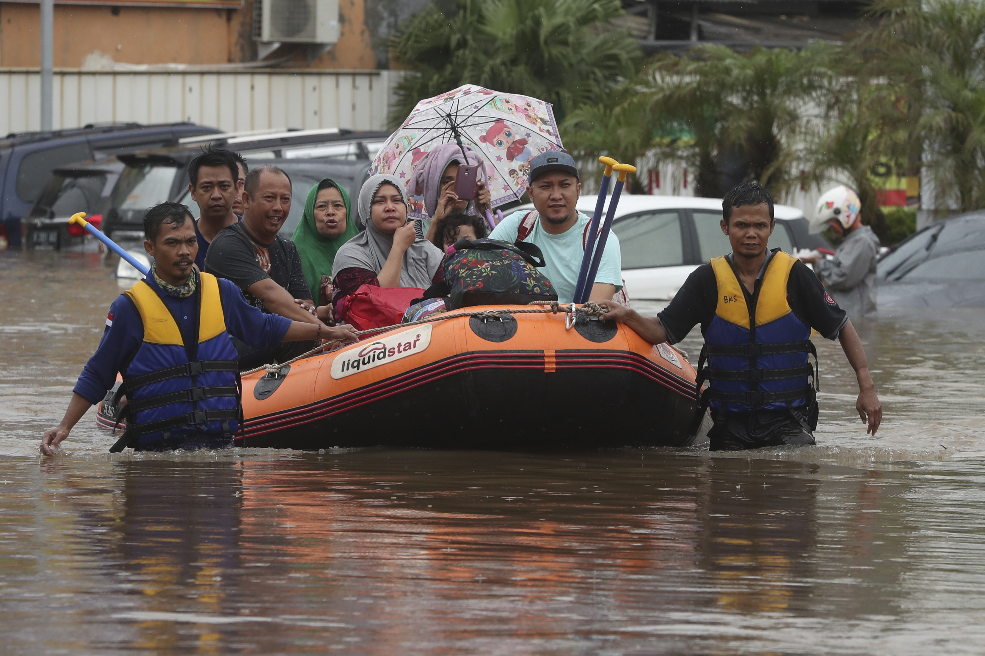 A rescue team evacuates residents from their flooded house at Jatibening on the outskirts of Jakarta, Indonesia, on Jan. 1, 2020.