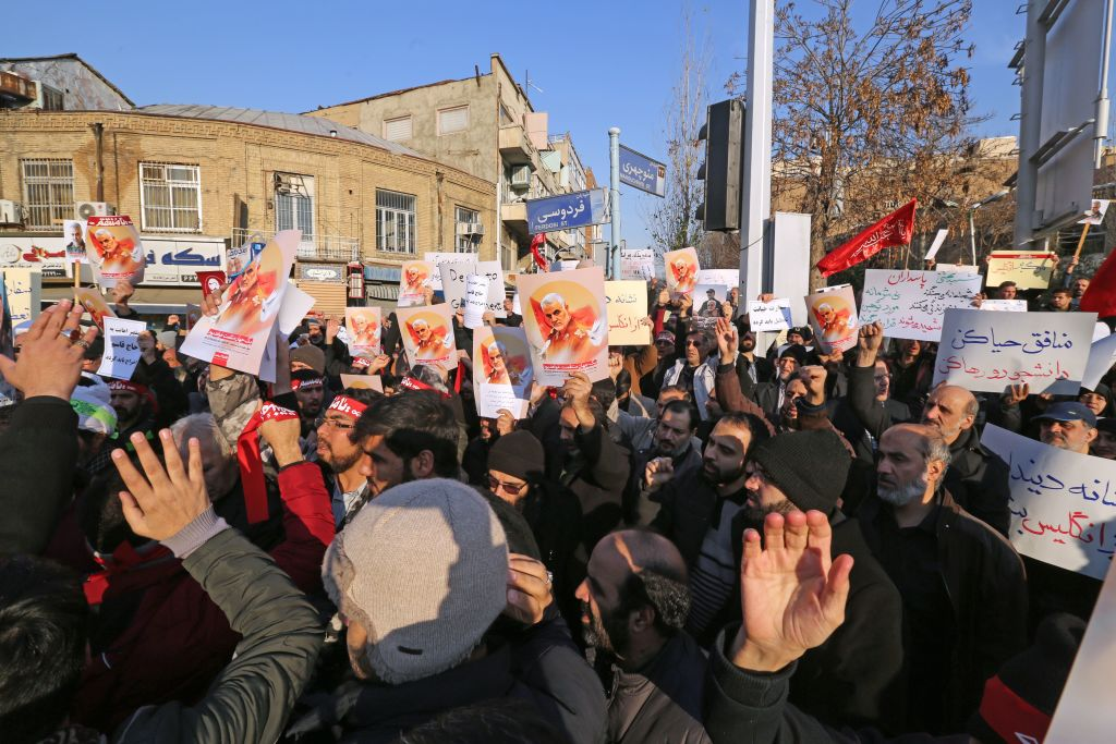 Iranian demonstrators hold placards bearing the image of slain military commander Qasem Soleimani in front of the British embassy in Iran's capital Tehran on Jan. 12, 2020.