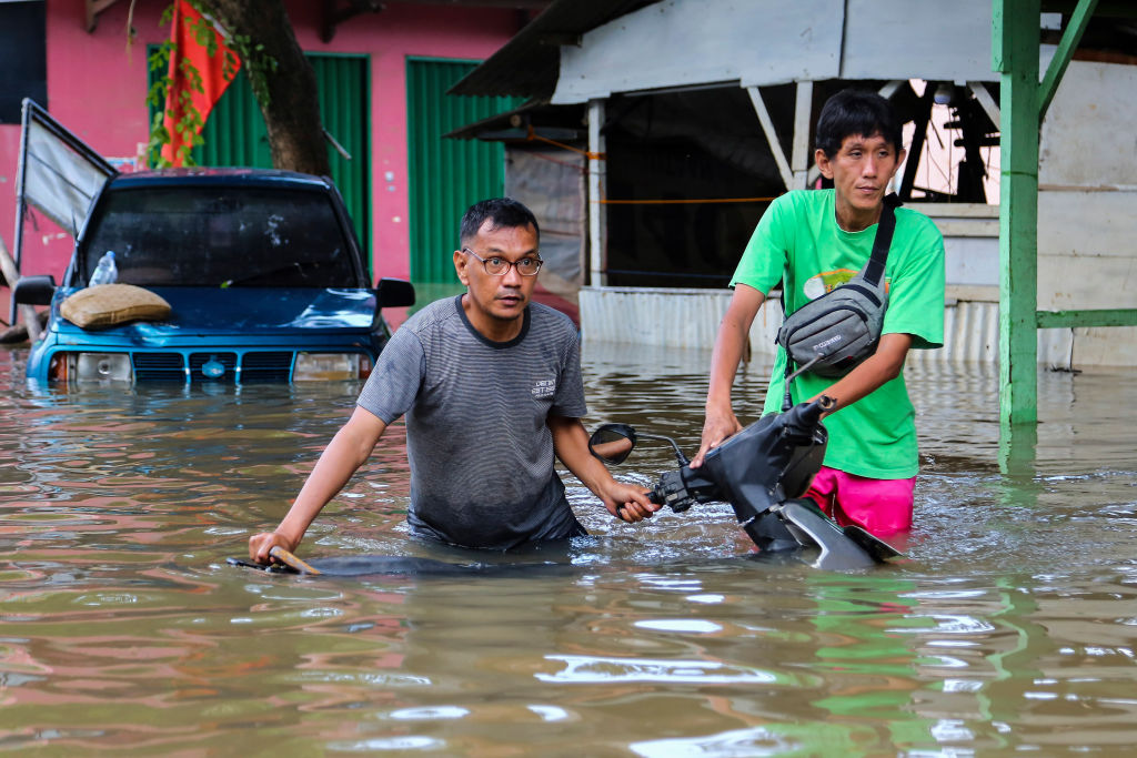 Two men push a motorcycle through floodwaters in Tangerang City in the Indonesian province of Banten on Jan. 2, 2020.